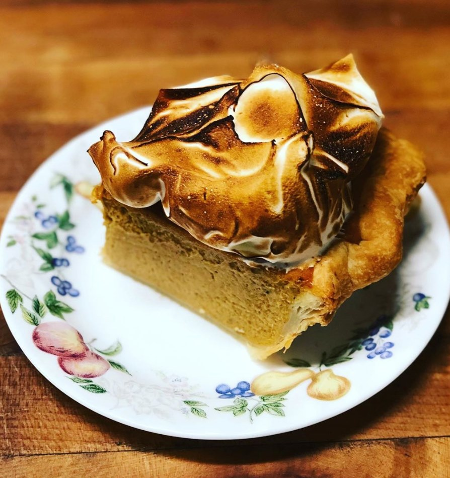 A slice of pie with a toasted meringue top on a vintage China plate