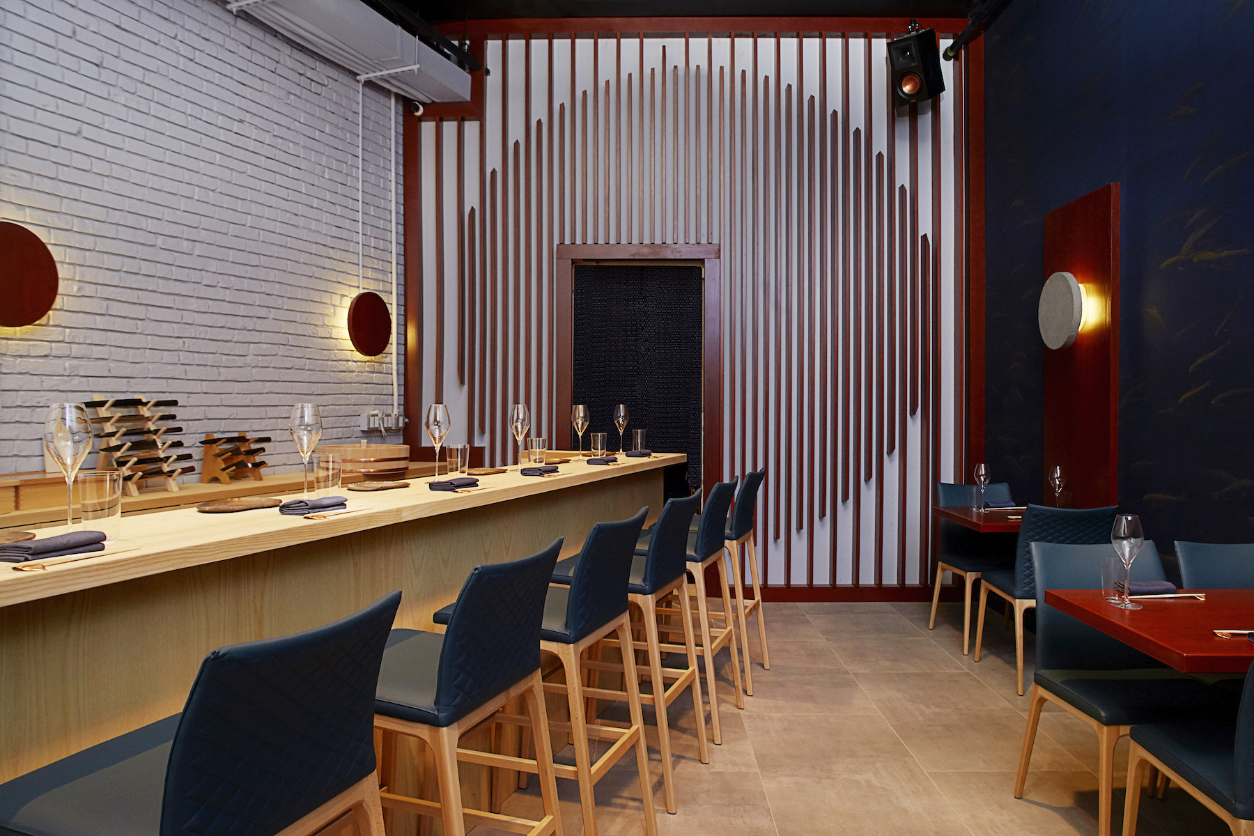 Inside a restaurant with white and red striped walls, tall green chairs propped up against a wooden counter and on the opposite side some more green chairs against red tables