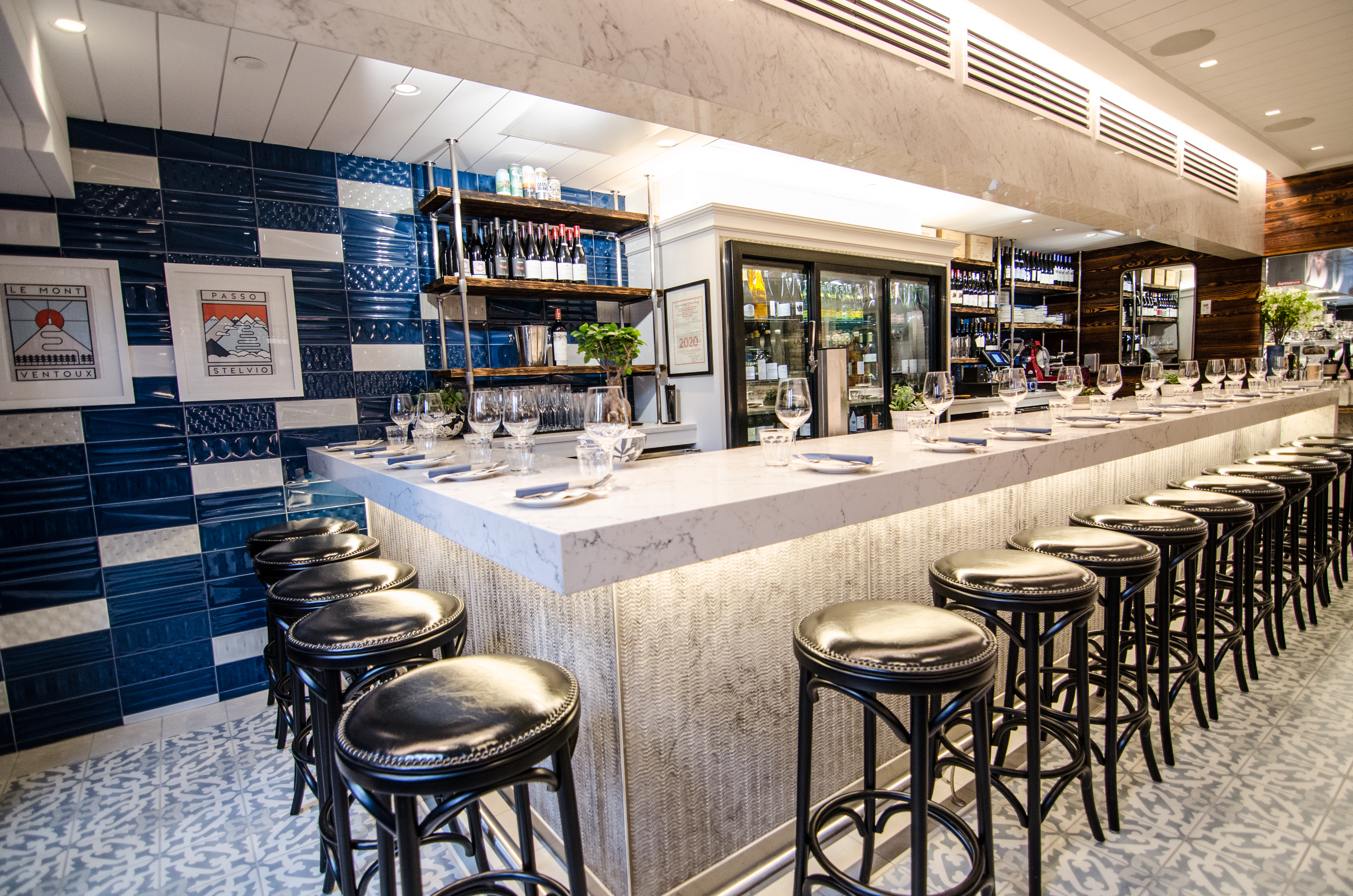 Shiny black stools line a white marble bar. The floor has Spanish-style tiles, and there are dark blue, glossy tiles on the wall.
