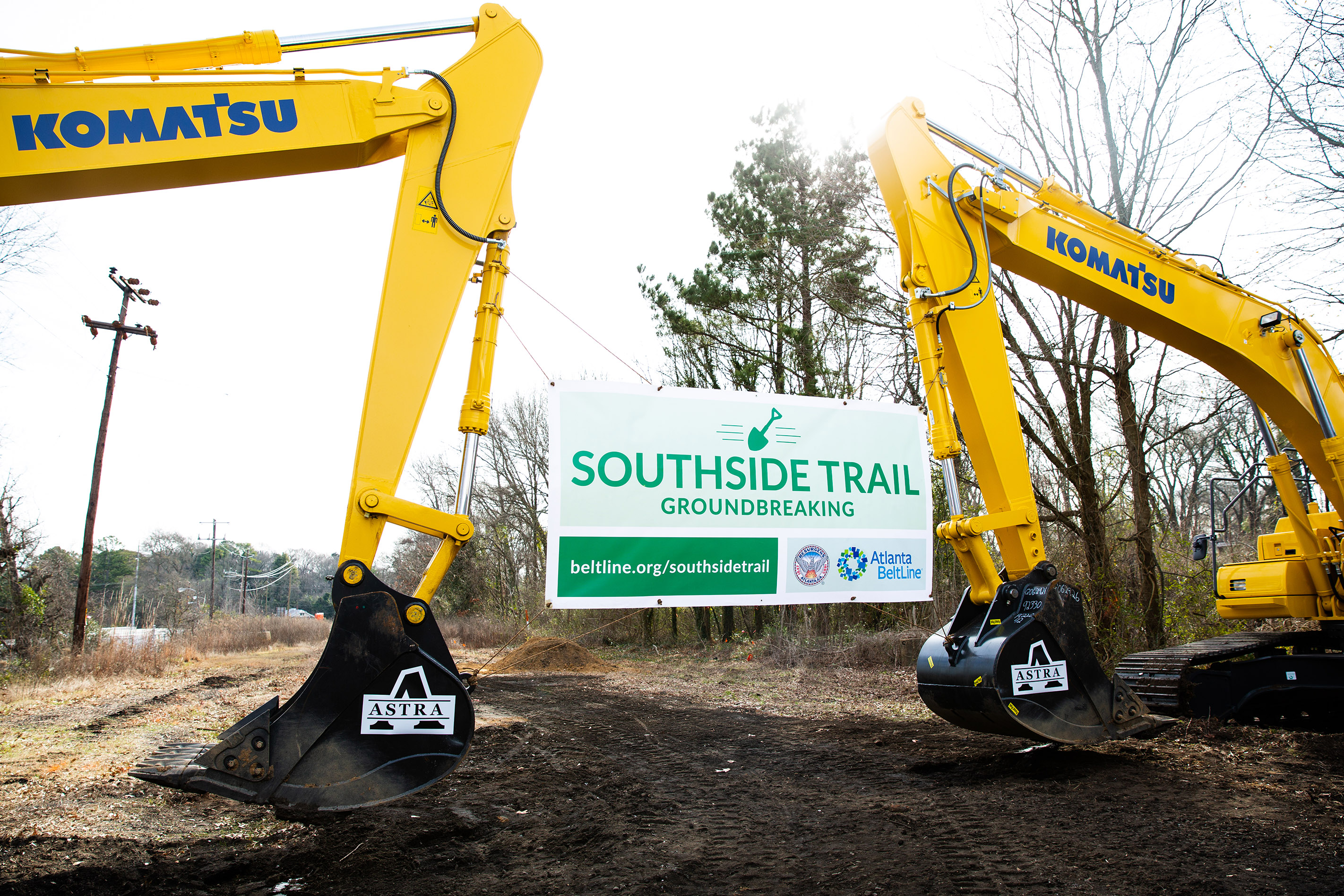 """Two backhoes support a sign that reads """"Southside Trail Groundbreaking."""""""