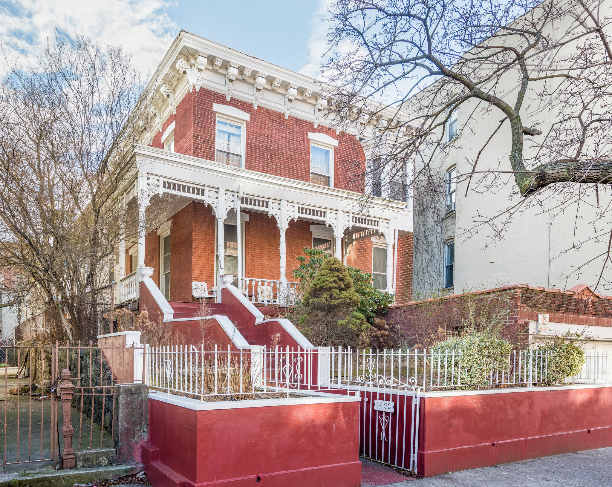A detached, two-story Italianate-style house with a wraparound porch and a few trees and plants around it.