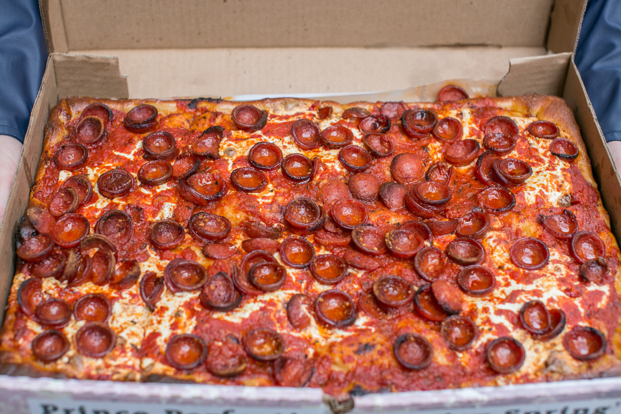 A full pie of square pizza with pepperoni cups.