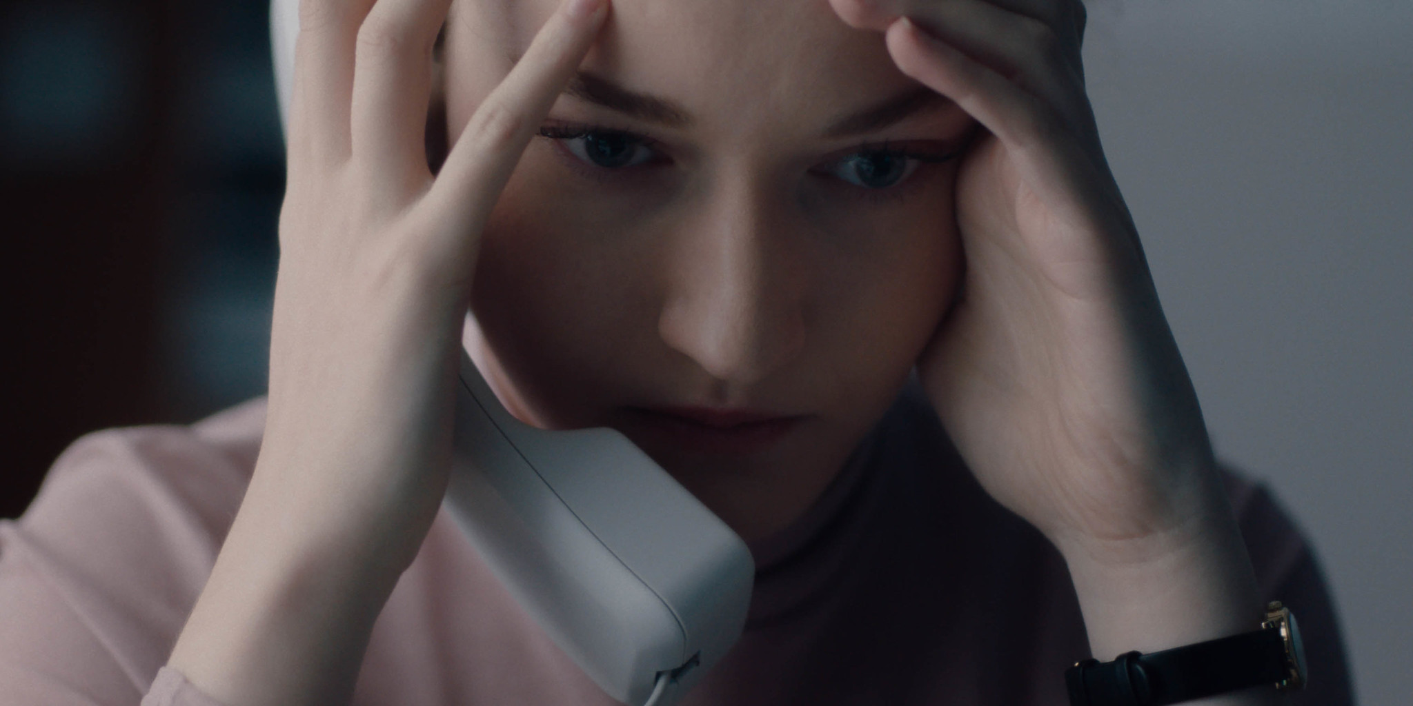A woman holds a phone receiver to her ear and her head in her hands.