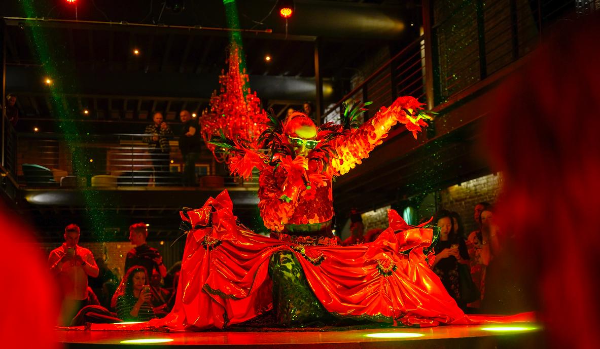red-lit performer in elaborate costume