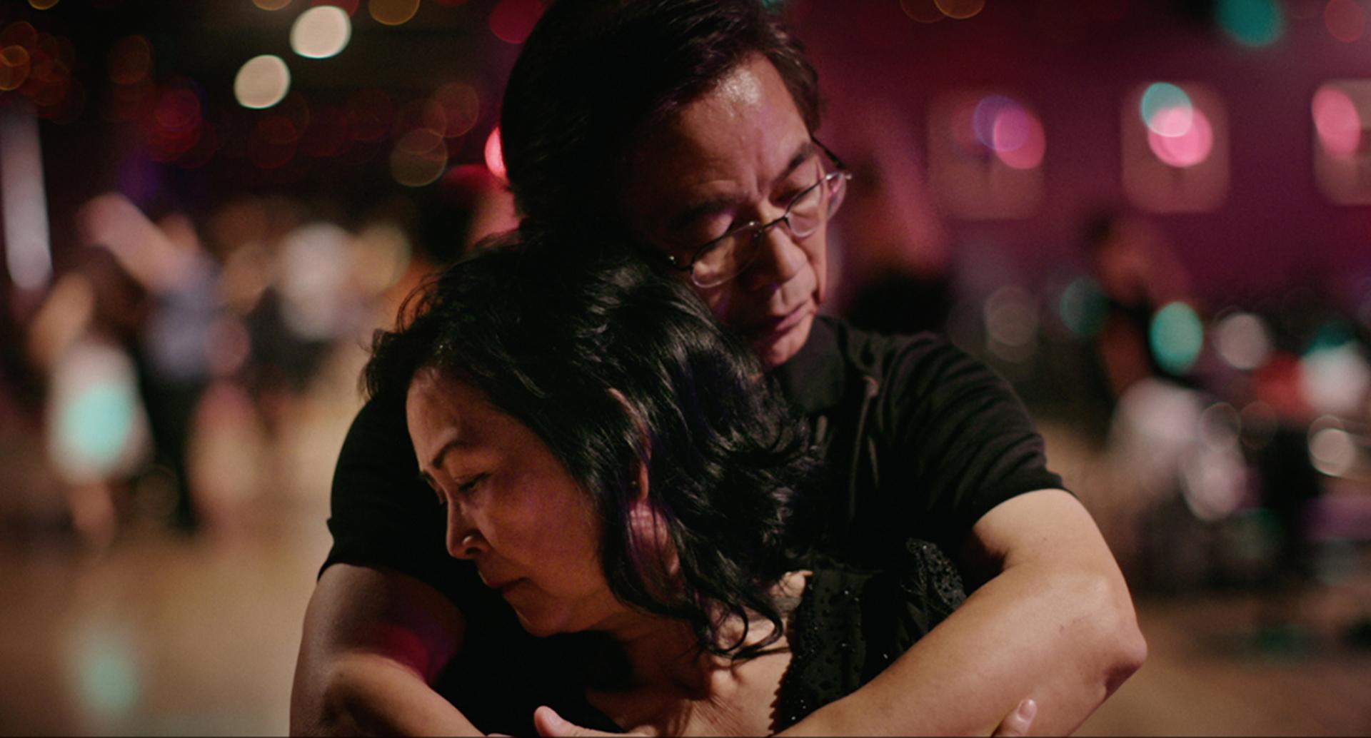 A couple hugs on a dance floor in the Oscar-nominated Walk Run Cha-Cha
