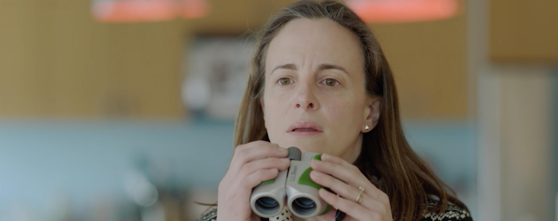 A woman peers over a pair of binoculars.