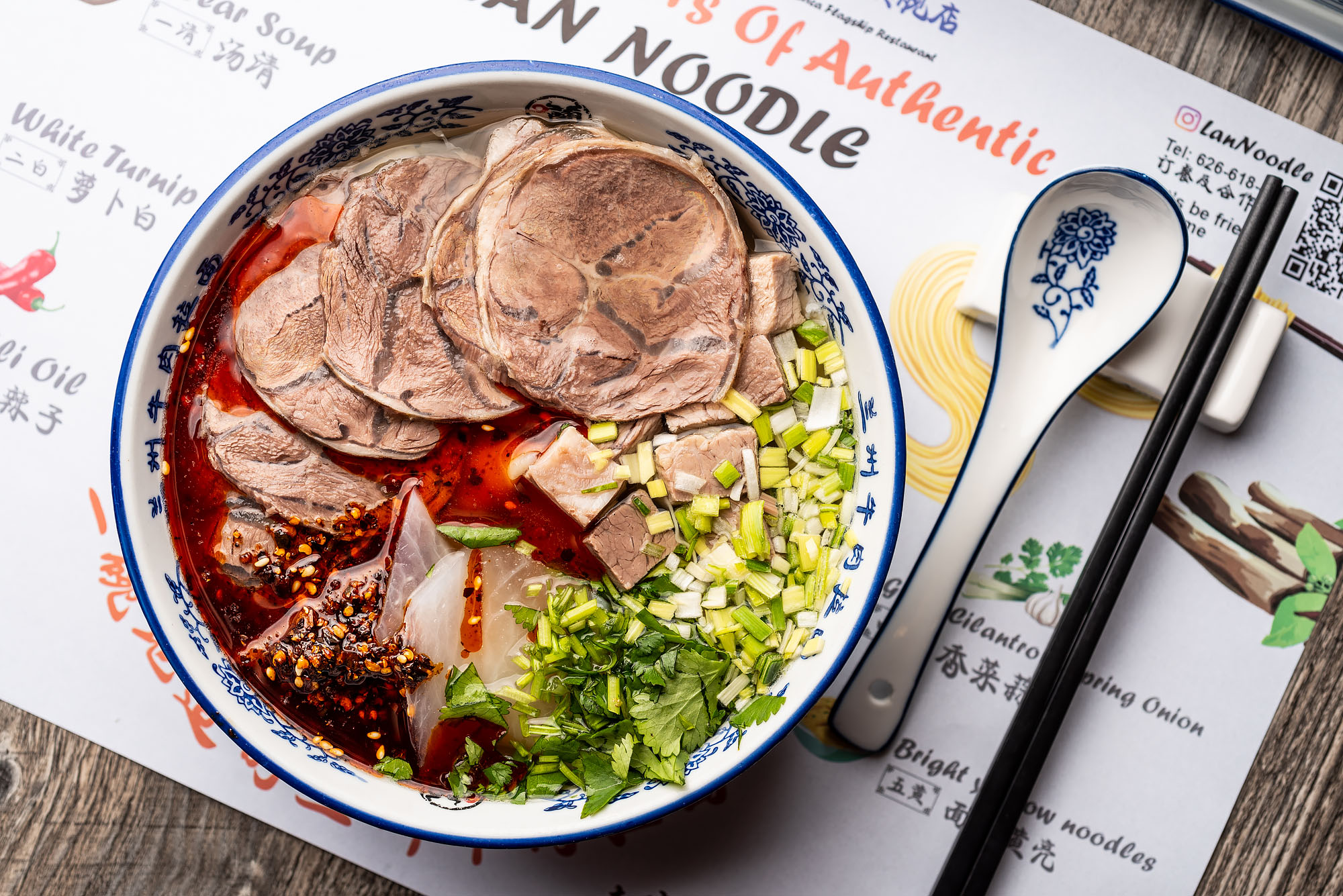 A bowl of Lanzhou beef noodle soup with meat and chile oil.