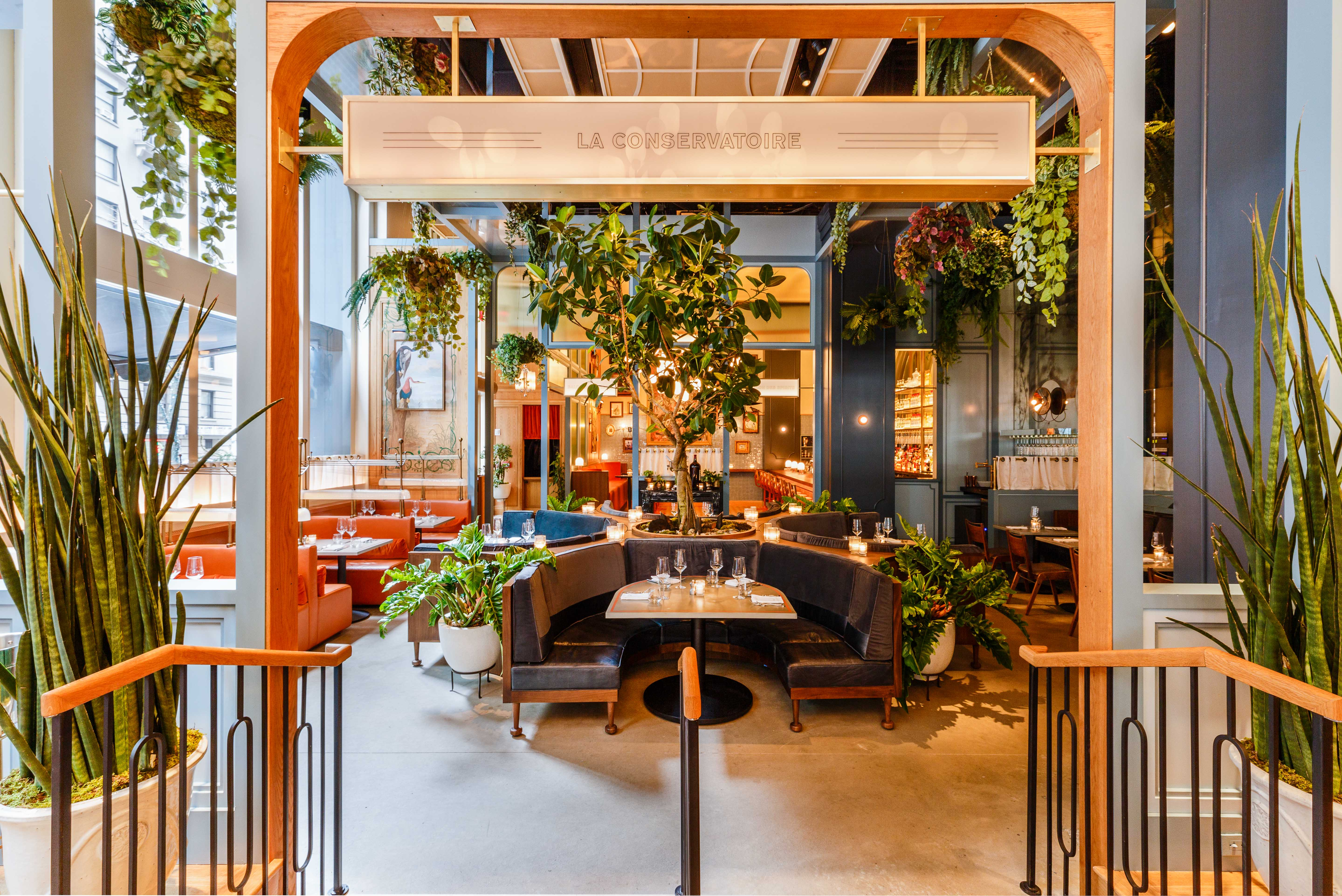 Railings lead into a big open dining room with U-shaped banquettes and lots of plants