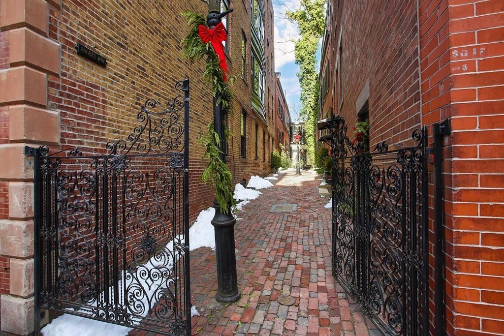 The entry of a narrow cobblestone street through an open wrought-iron fence.