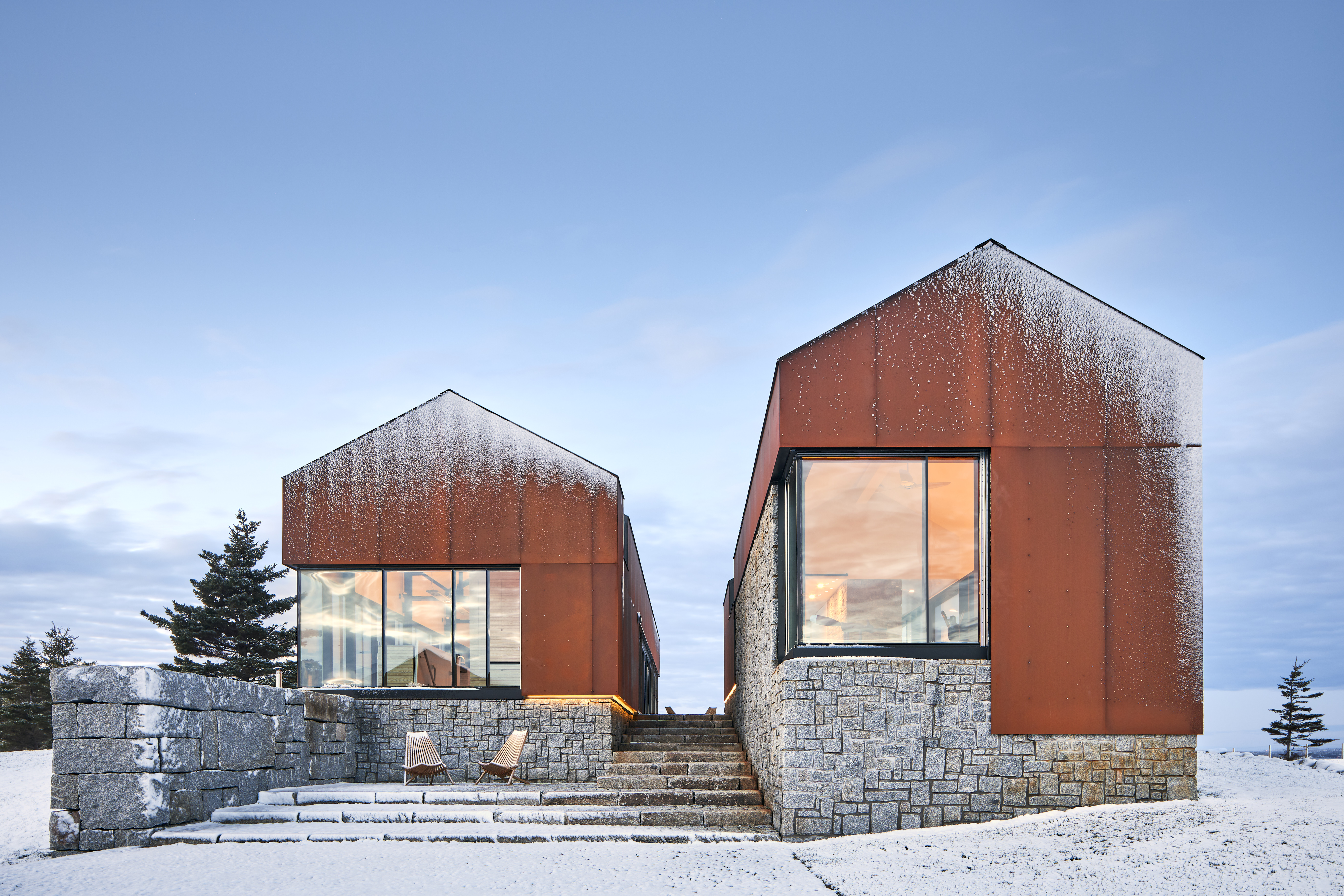 Two gabled barns with red siding and stone base.