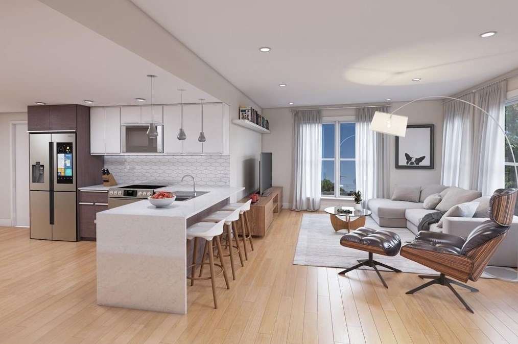 A rendering of an open living room-kitchen with furniture and a large counter separating the two rooms.