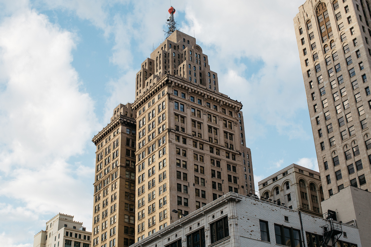 The exterior of the Penobscot building in Detroit. The facade is tan with a large red orb on the top.