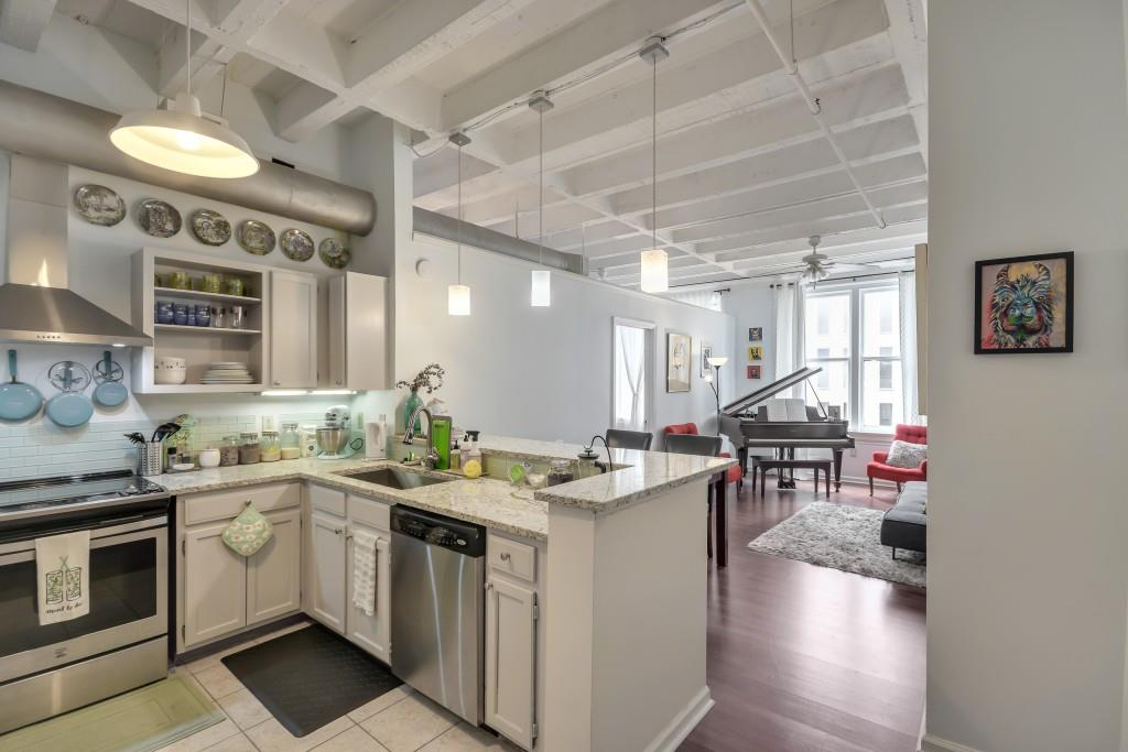A big white loft area with a kitchen at left and a piano at right.