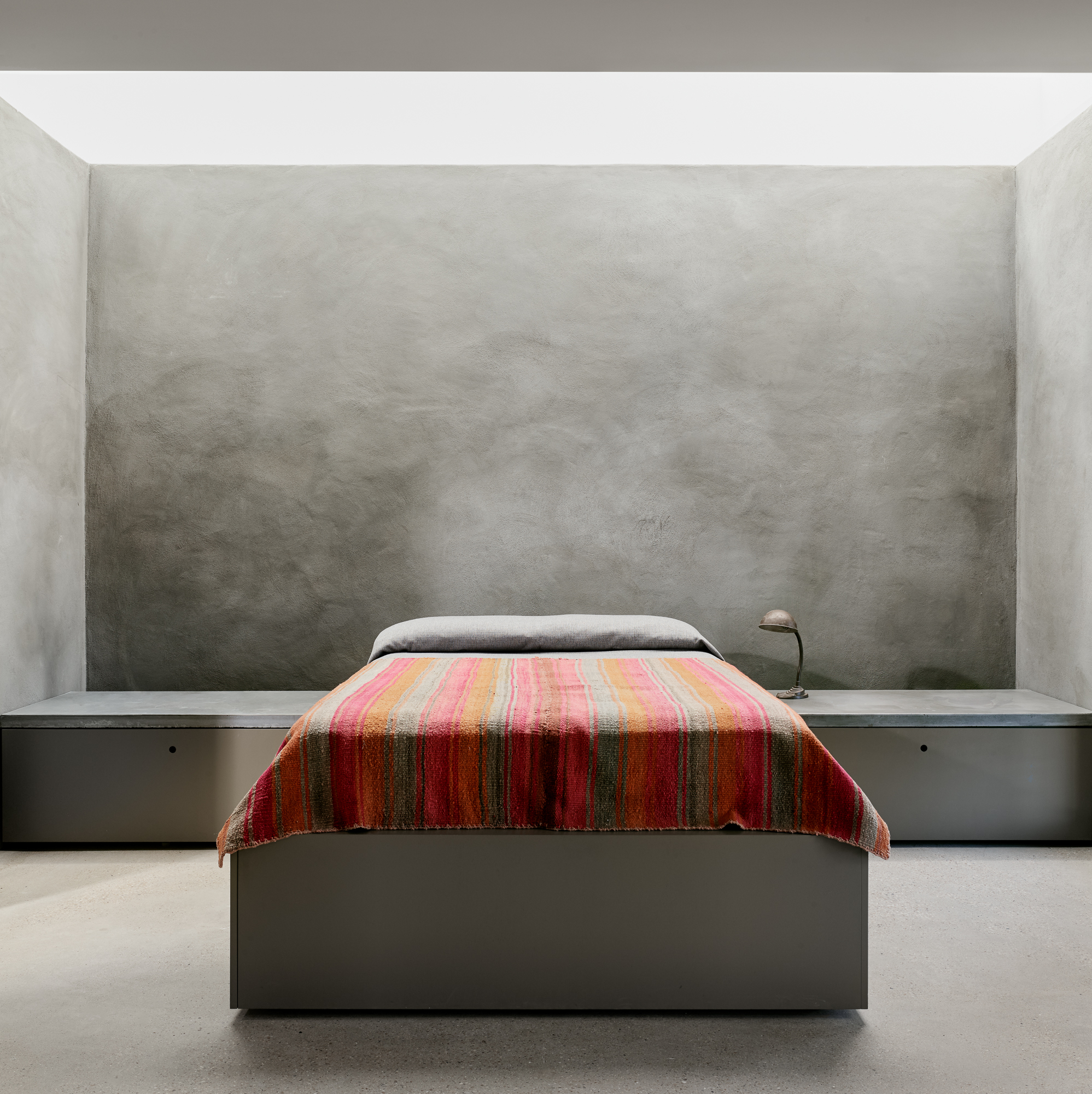 A minimalist bedroom with gray concrete walls and a bed with a pink patterned bedspread.