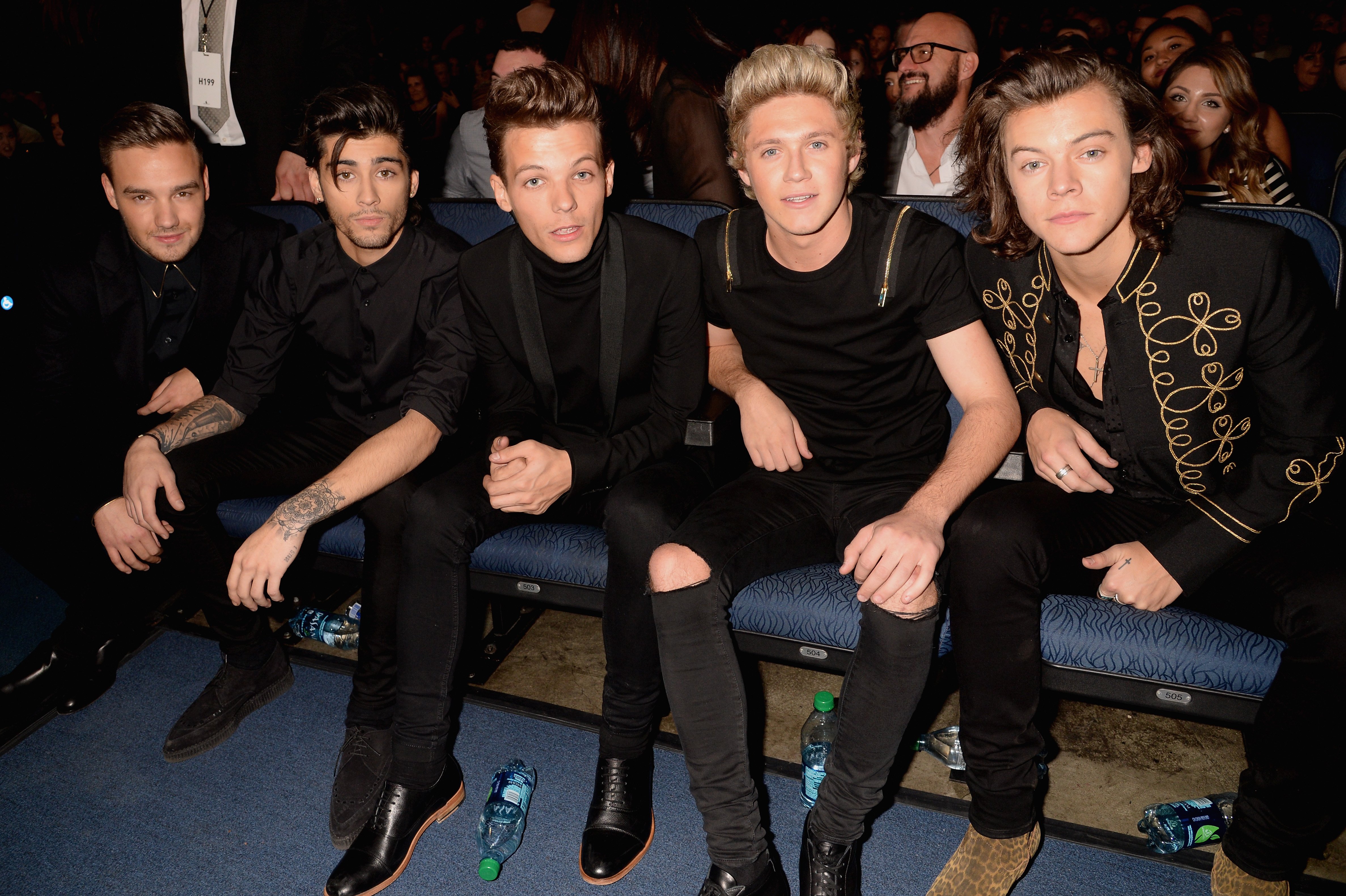 Liam Payne, Zayn Malik, Louis Tomlinson, Niall Horan, and Harry Styles of the music group One Direction all sitting on a bench at the 2014 American Music Awards in Los Angeles.