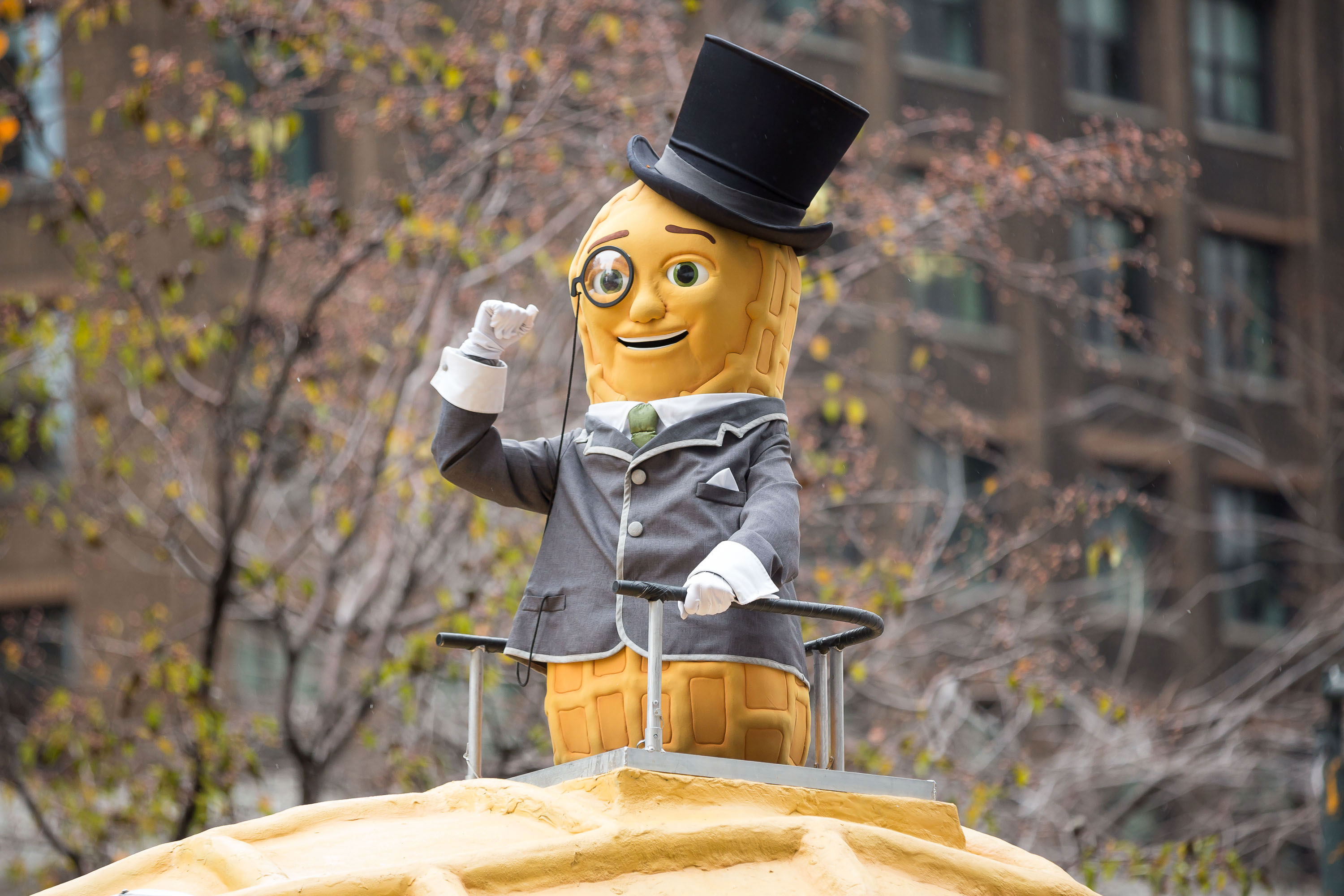 Planters' Mr. Peanut mascot standing on a Nutmobile float in a parade.
