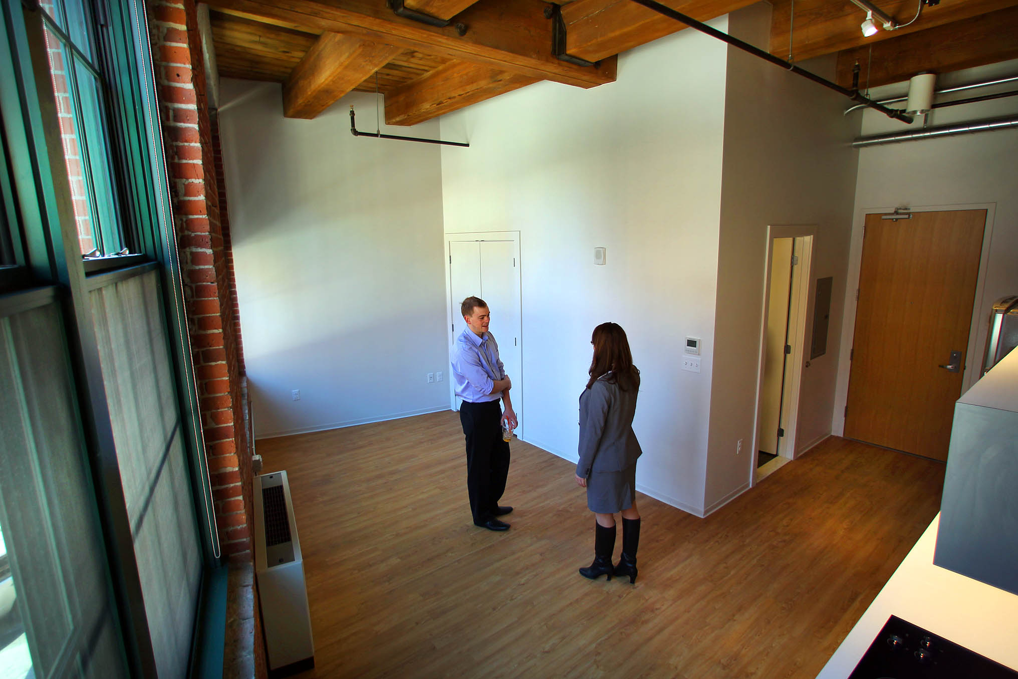 A very small and empty apartment with two people standing in the middle of it.