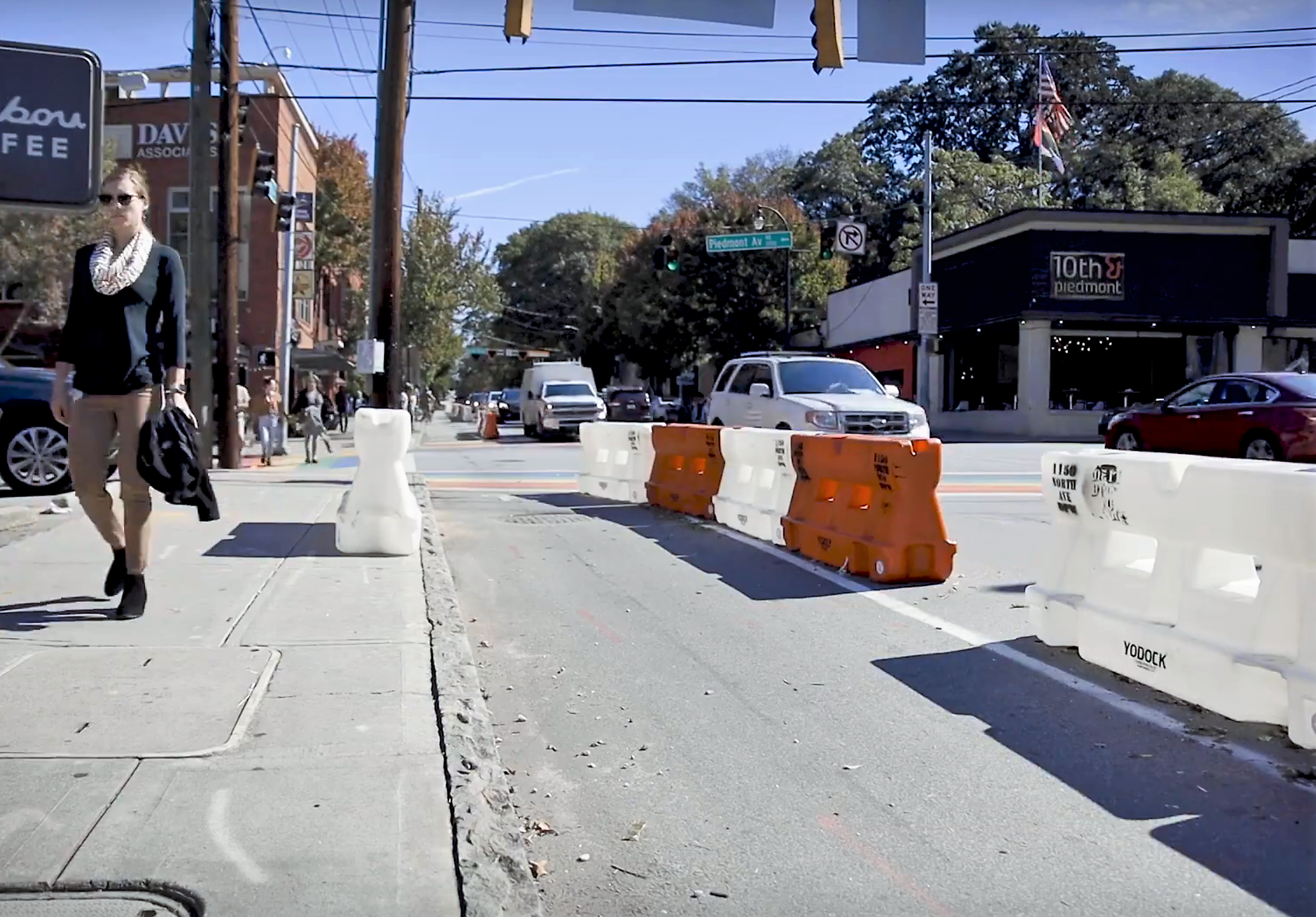 Orange and white plastic barriers cordon off an automobile lane to make a temporary bike path.