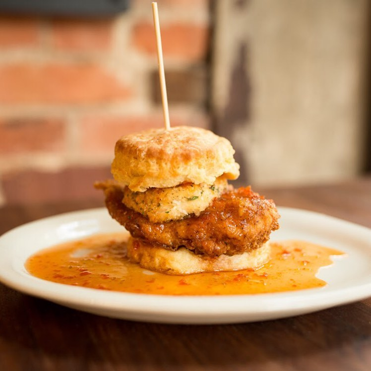 A photo of a fried chicken biscuit topped with fried goat cheese and  pepper jelly on a white plate