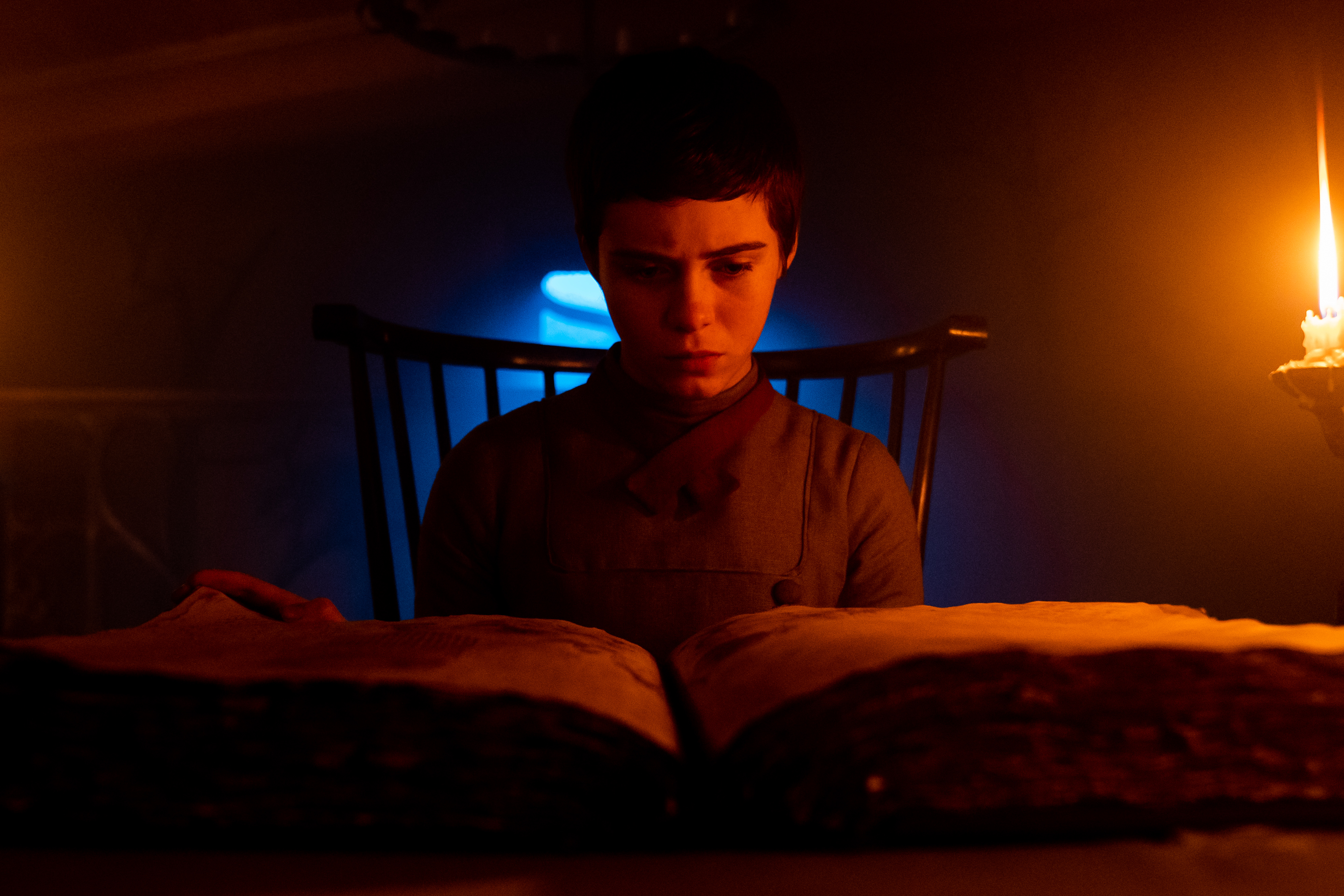 a young woman with short dark hair looks over a book in a dim, red-lit room that turns her face the color of blood in Gretel & Hansel