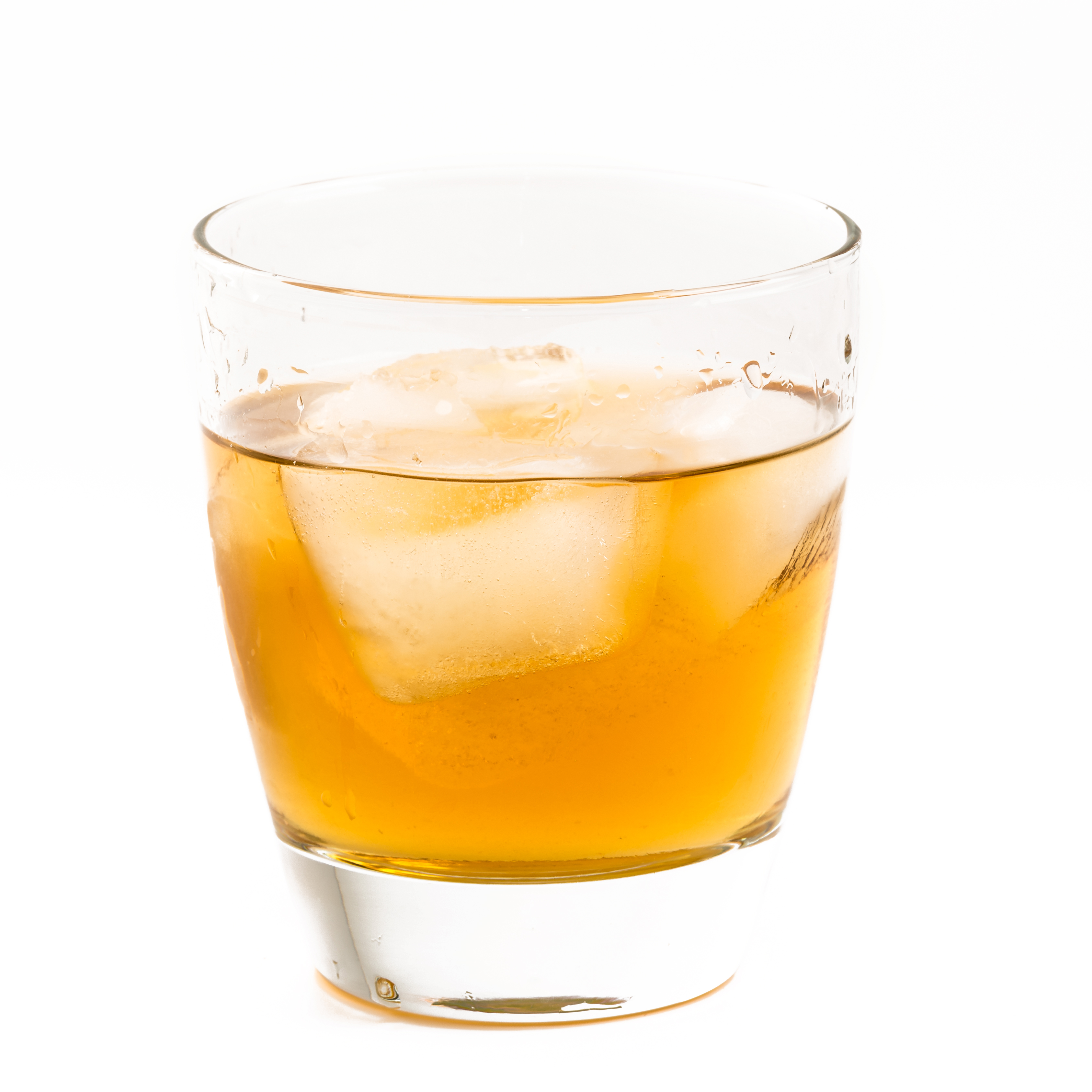 Old fashioned glass with whisky on the rocks served...