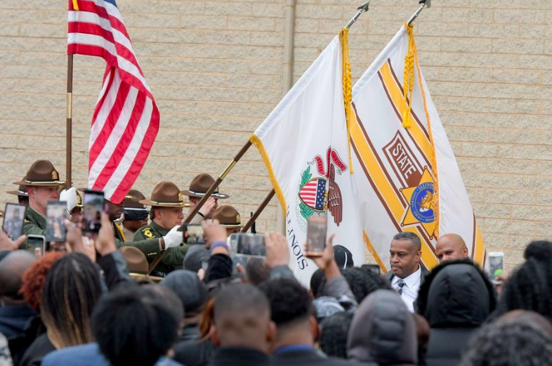 The state of Illinois and State Police flags are lowered as the casket of retired Illinois State Police Trooper Gregory Rieves passes upon exiting the Rock of Ages Baptist Church in Maywood where the retired officer's funeral was held on Saturday.