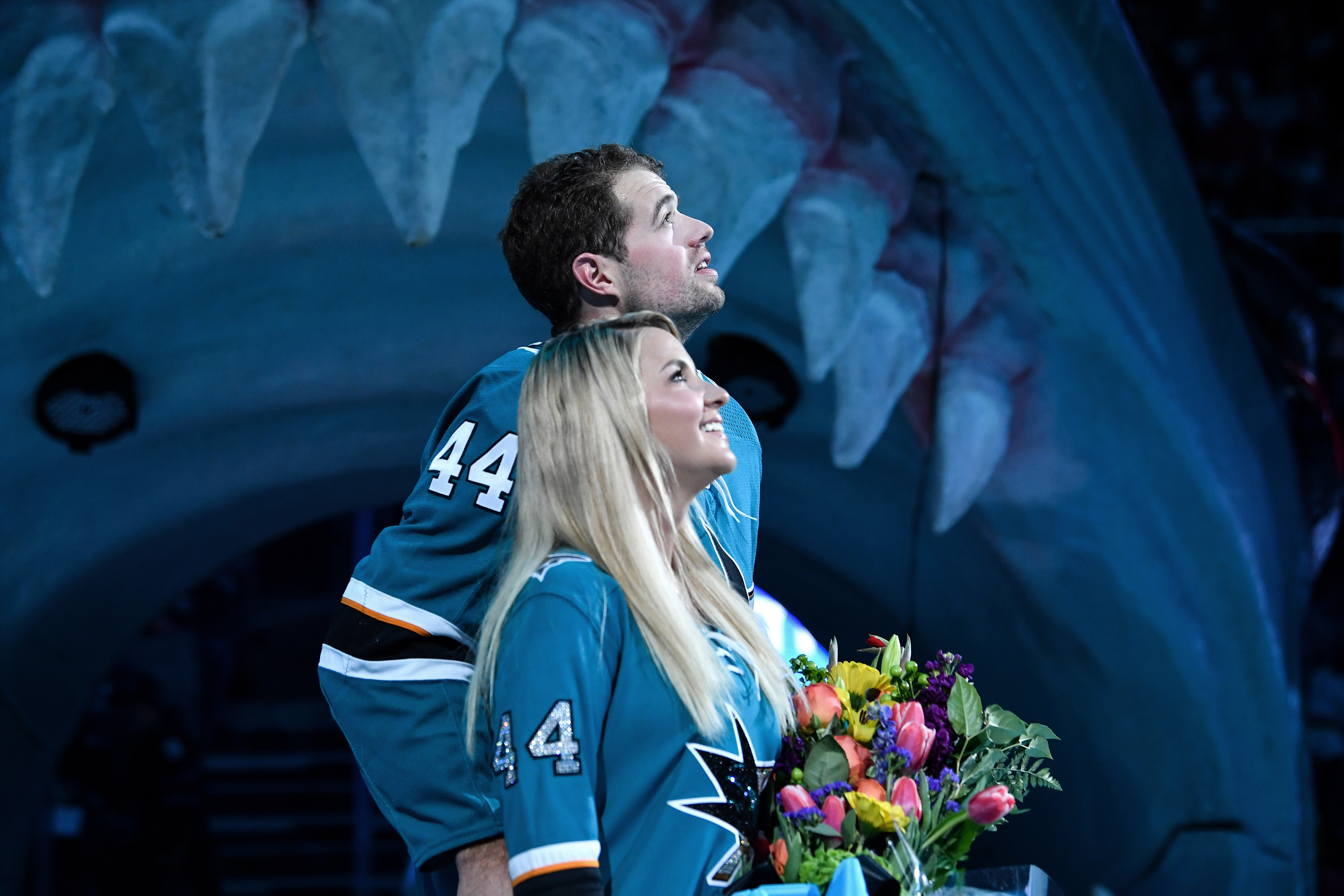 Marc-Edouard Vlasic #44 of the San Jose Sharks and his wife Martine Vlasic look up at the scoreboard while being honored for playing in 1,000 NHL games before the game against the Tampa Bay Lightning at SAP Center on February 1, 2020 in San Jose, California.