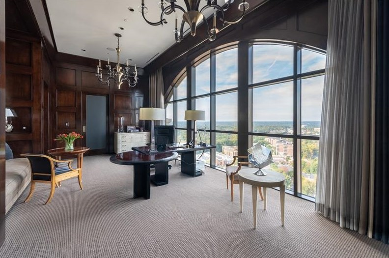 Home office with floor-to-ceiling windows overlooking the city.