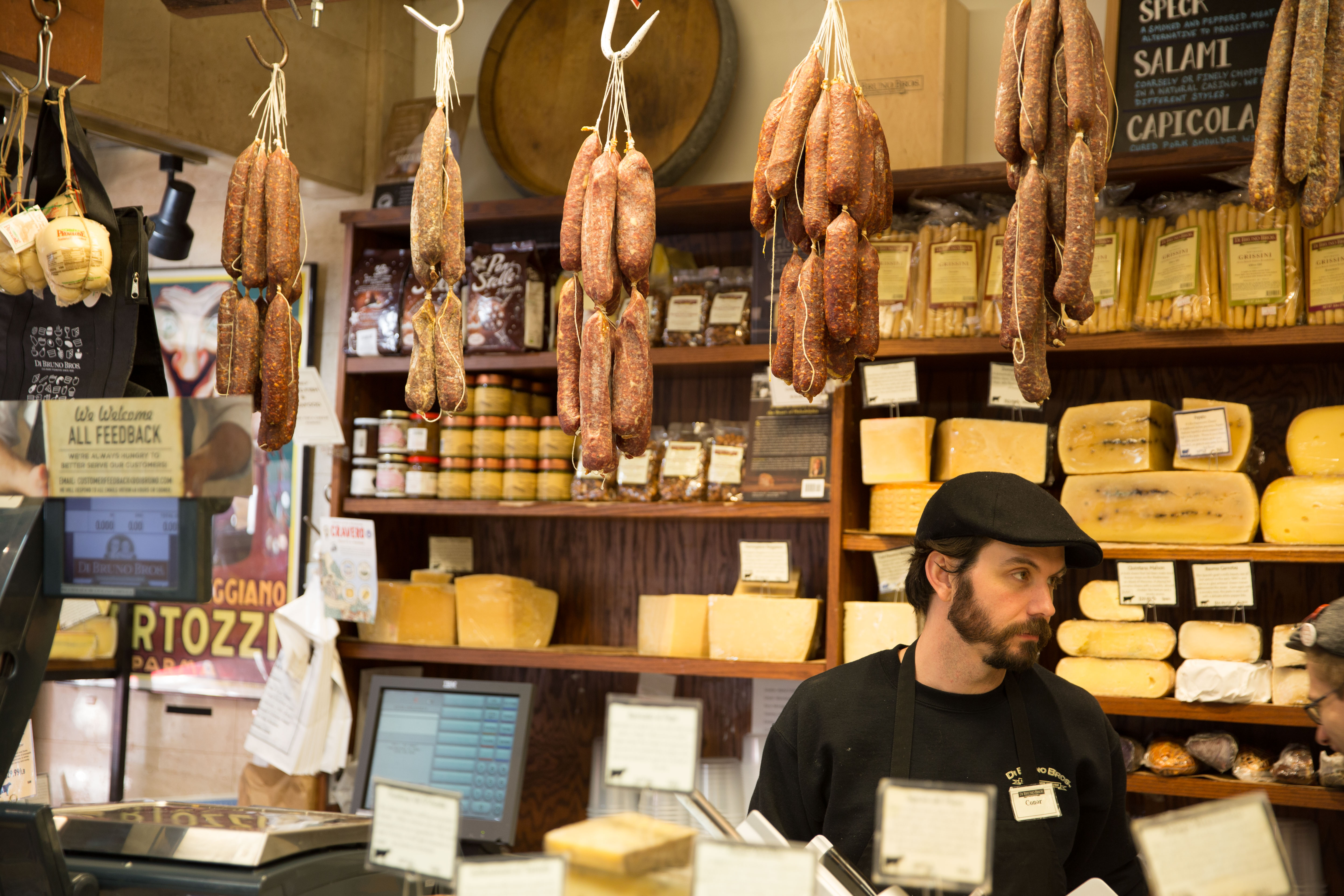 man standing behind counter at cheese and meat shop