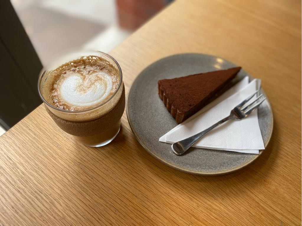Coffee and a slice of chocolate tart on a gray plate with a fork.