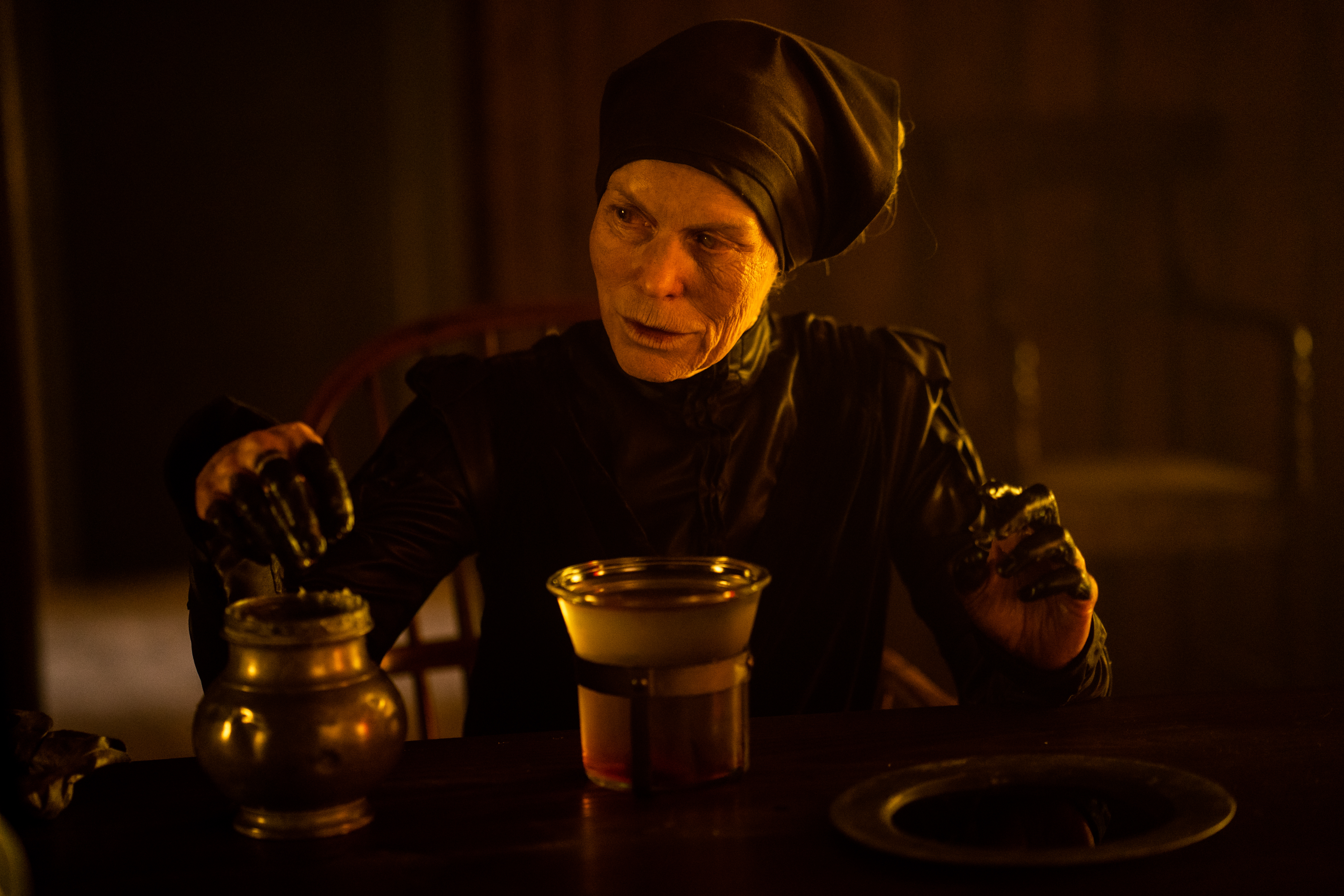 The Witch in Gretel and Hansel, an elderly woman dressed in a black robe and head-wrap, dips her blackened fingers into a brass pot full of goo.
