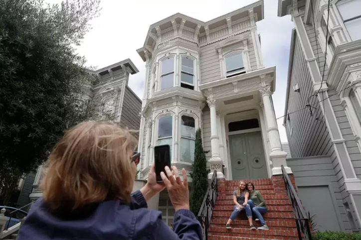 Two people hugging while sitting on the steps of a white Victorian house with red brick steps. A third person in the foreground is taking their picture, her back turned toward us.