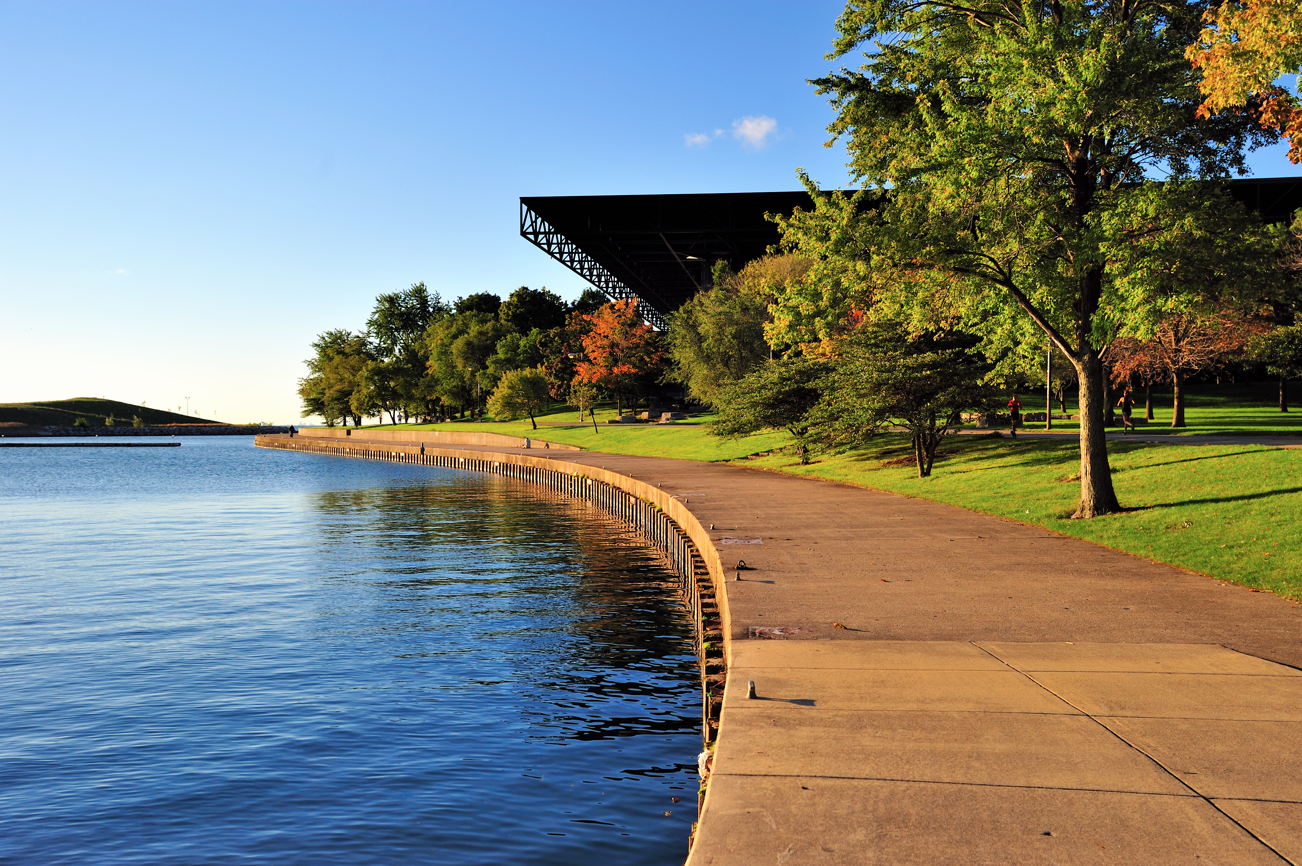 A modernist space-frame building with a flat overhanging eave next to a large body of water.