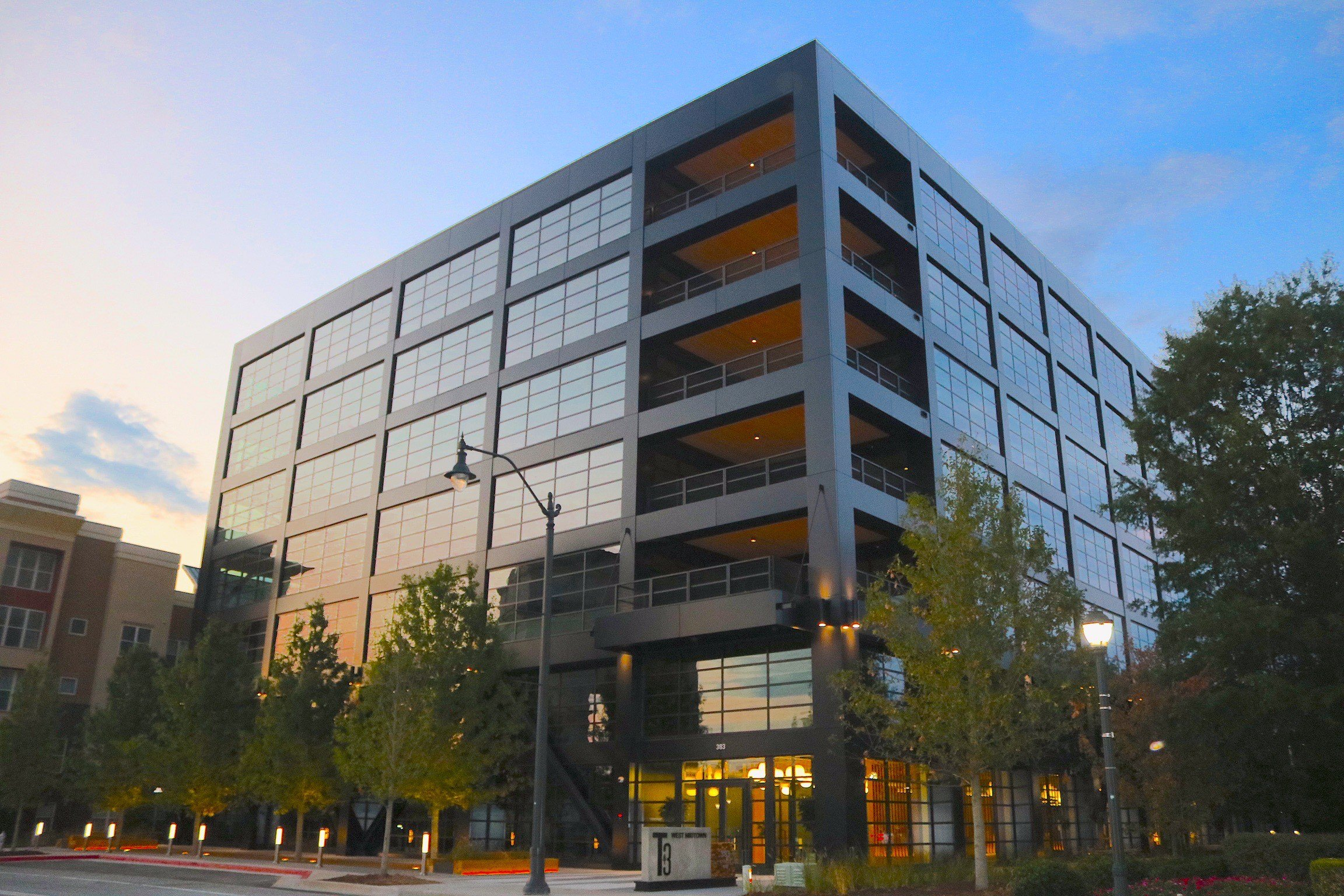 A ground-level view of the new office building, which stands seven stories and is wrapped in black metal and large windows.