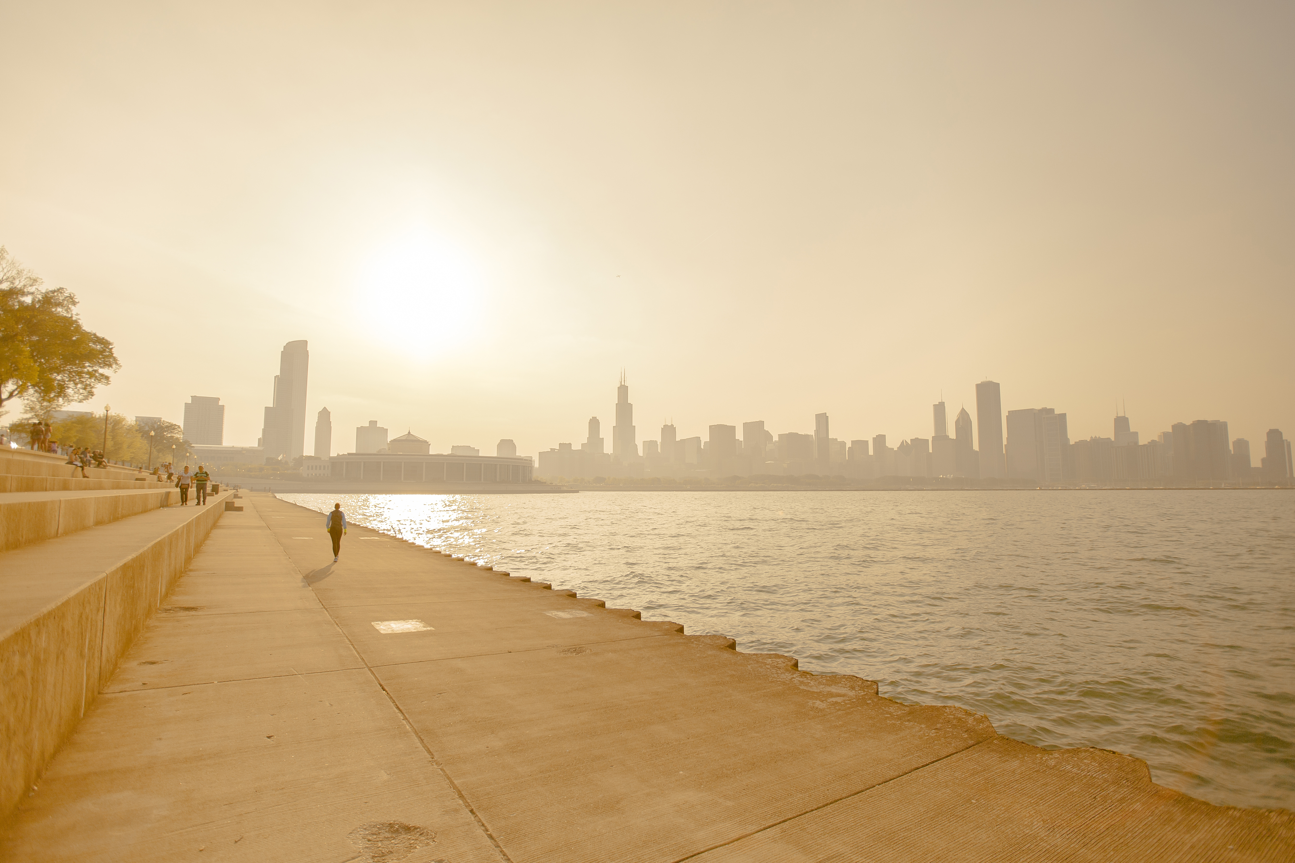 People walk along the lake near Chicago on a hot summer day under a bright sun.