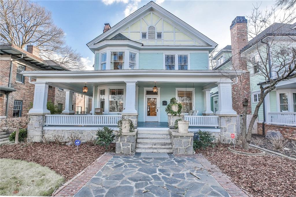 A huge blue Victorian home with a stone walkway and large chimneys.