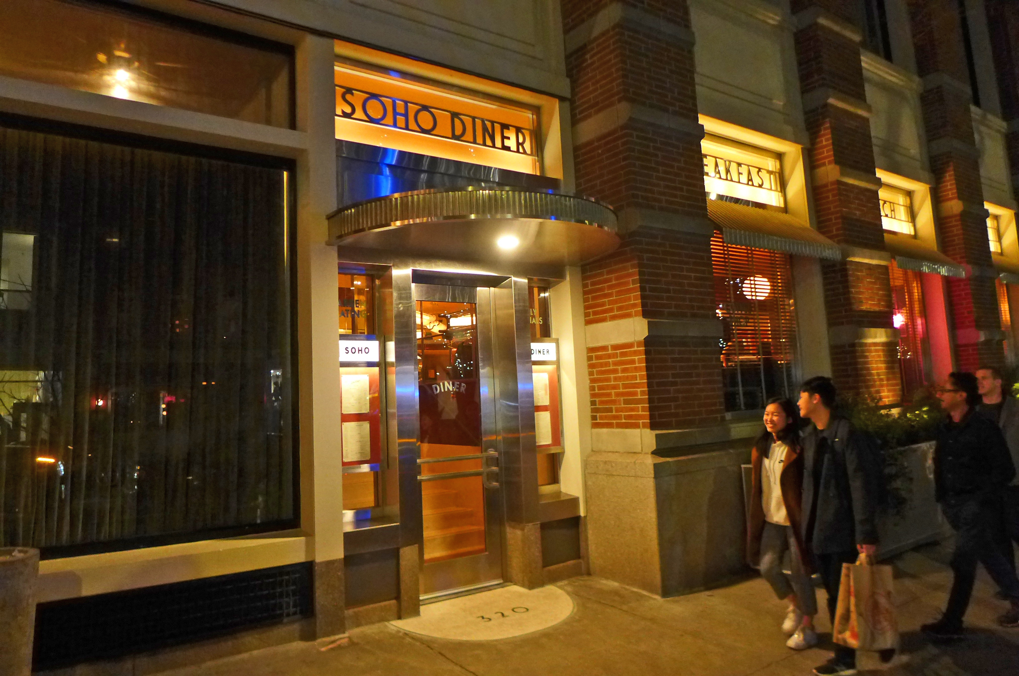 A darkened facade of a diner in a hotel, with laughing people passing by on the sidewalk.