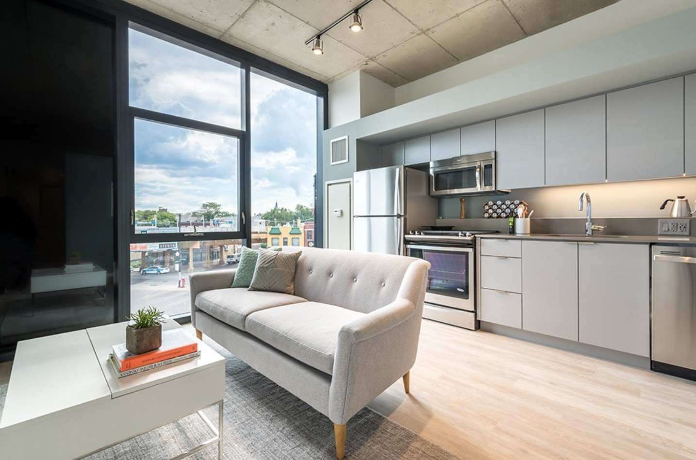 An open kitchen and living room with a small sofa, grey cabinets, and a large floor-to-ceiling window.