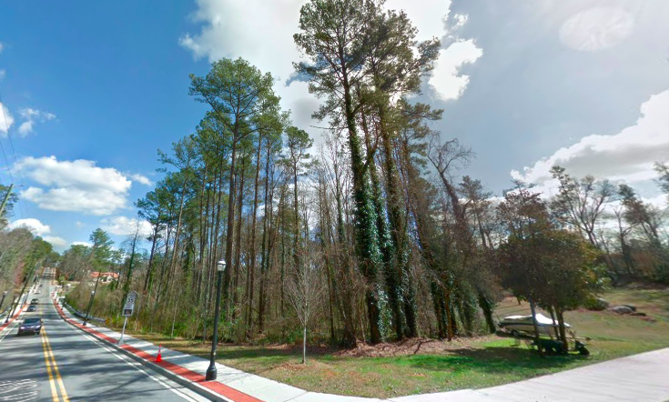 A wooded lot with tall trees and houses in the distance.
