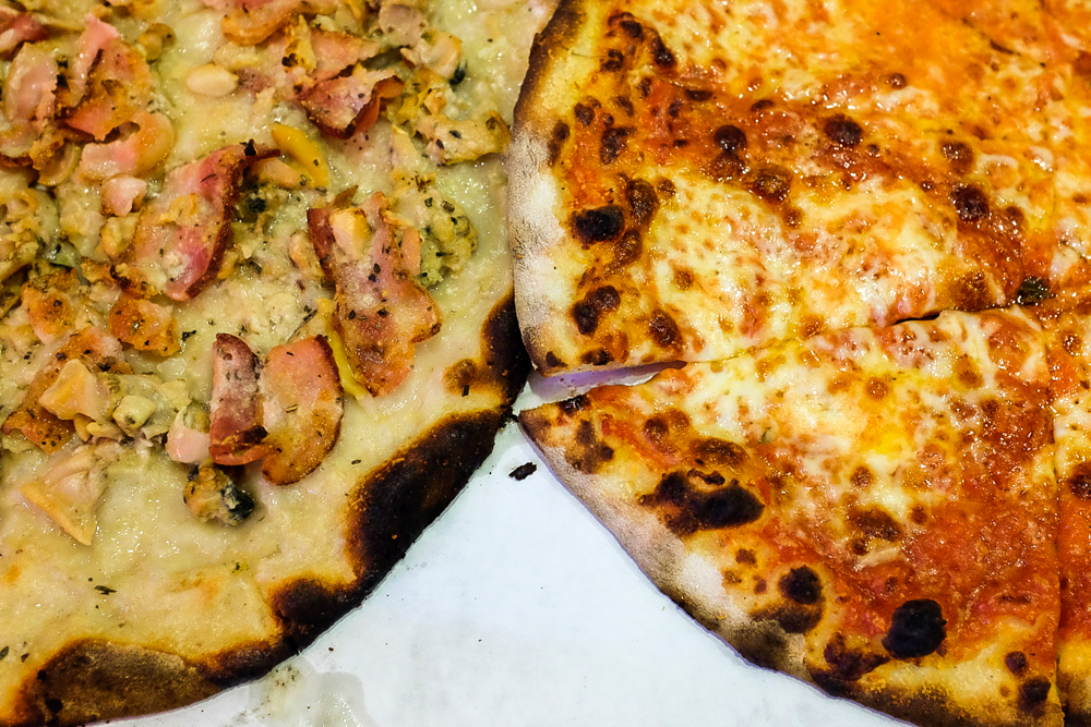 Overhead view of two New Haven-style pizzas with charred crust. One is topped with clams.