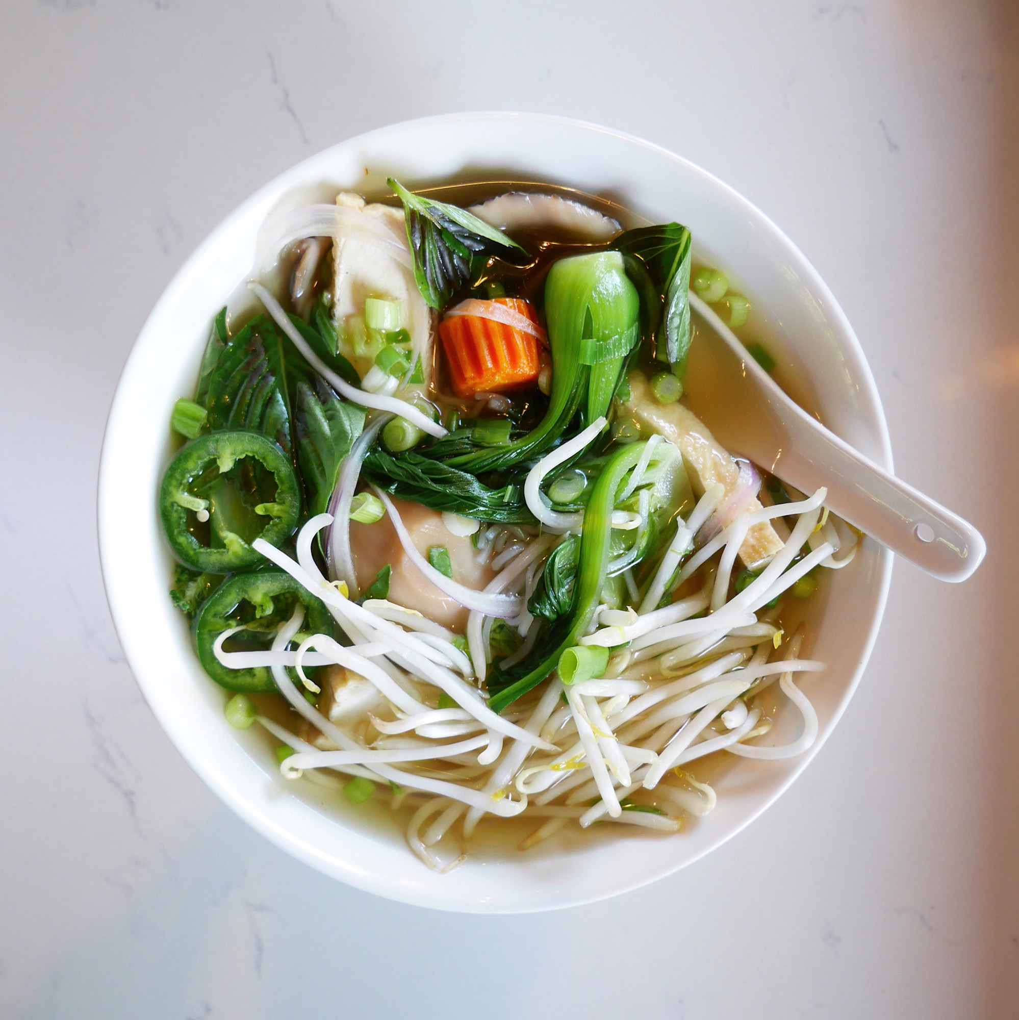 A photo of vegan pho at Anchoi Kitchen + Bar, which comes with baby bok choy, bean sprouts, and slices of bright-green jalapeno