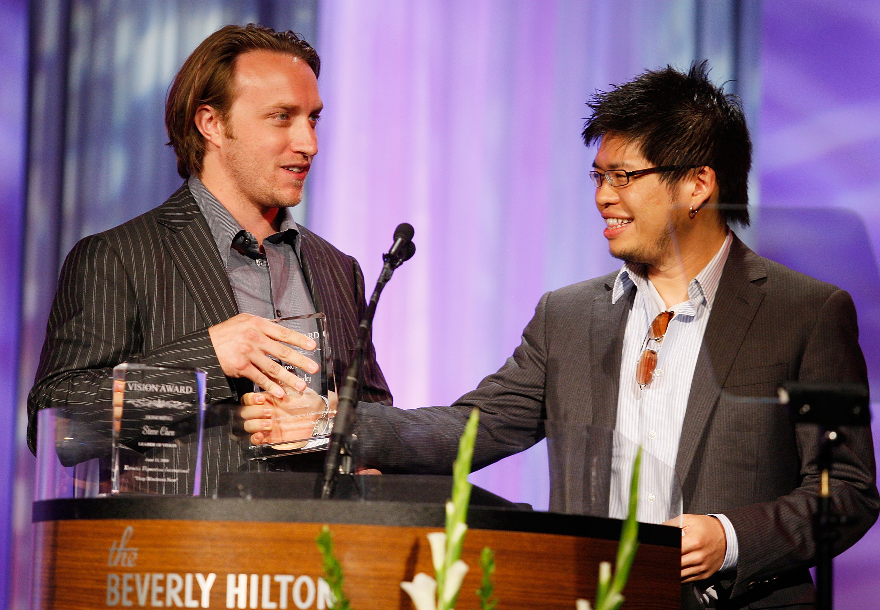 YouTube co-founders Chad Hurley and Steve Chen stand at a podium to accept an award in 2008.