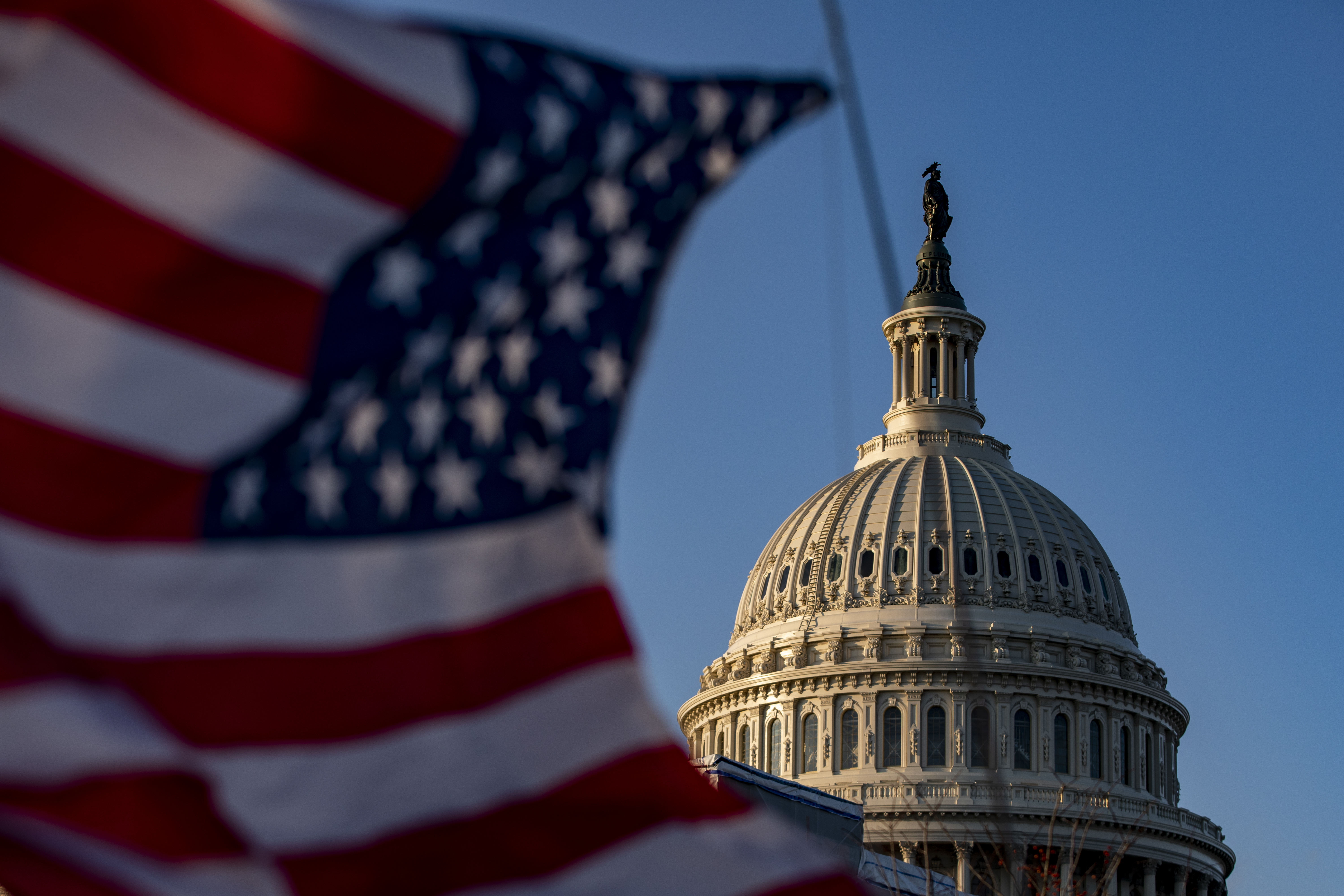 An American flag waves with the Capitol Building in the background.