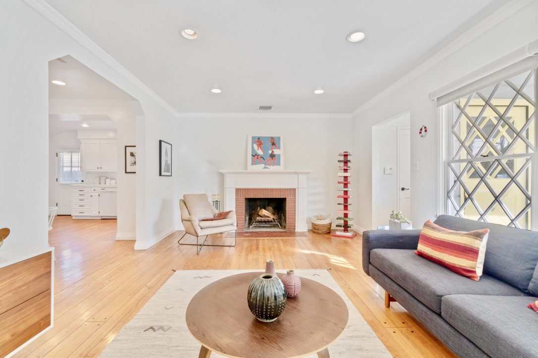 A room with white walls and a brick fireplace at the far end. A gray sofa can be seen on the right