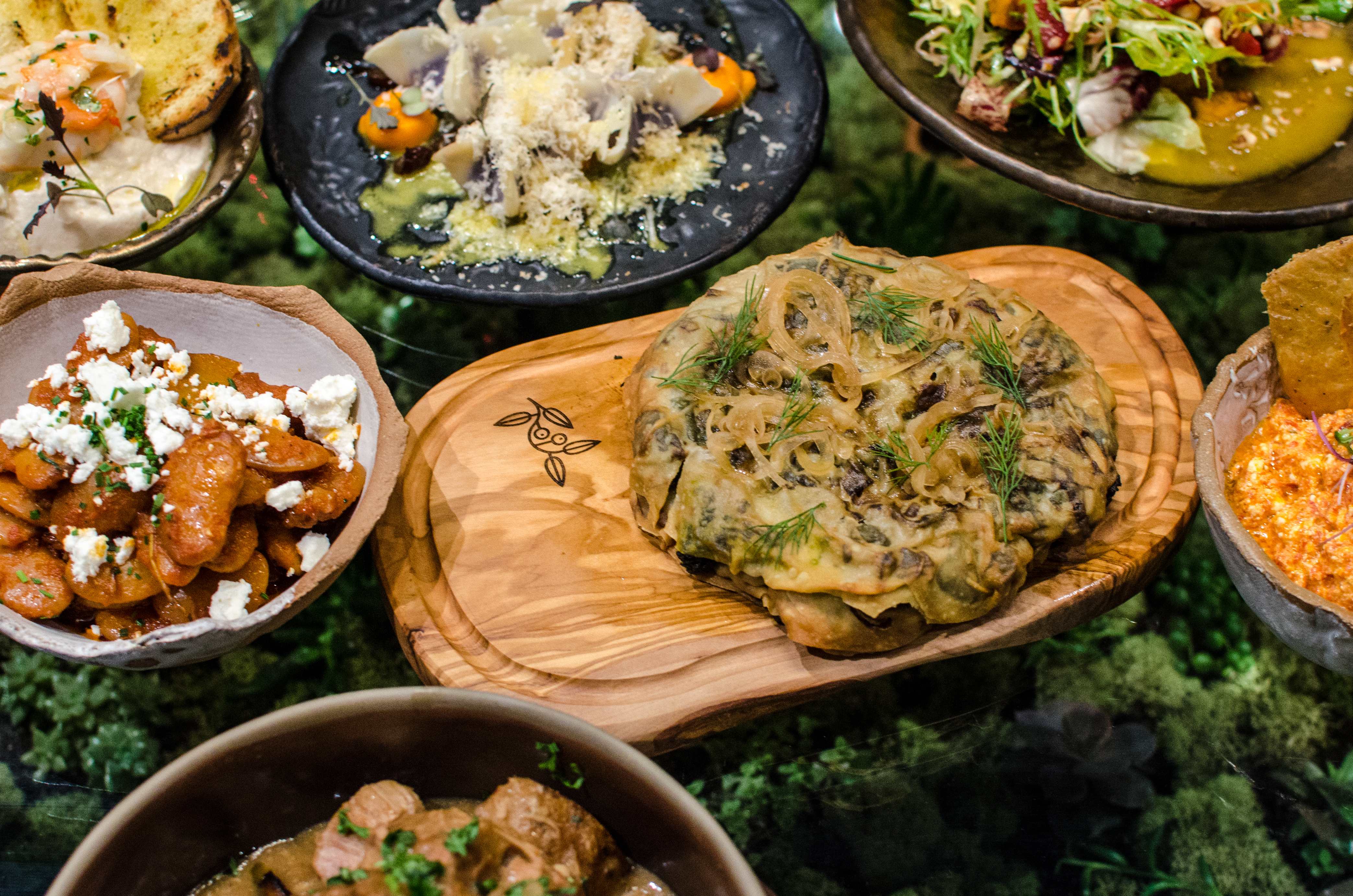 A spread of Greek food on a clear glass table over a platform of greenery. The dishes include a wild greens pie, gigantes, and more.