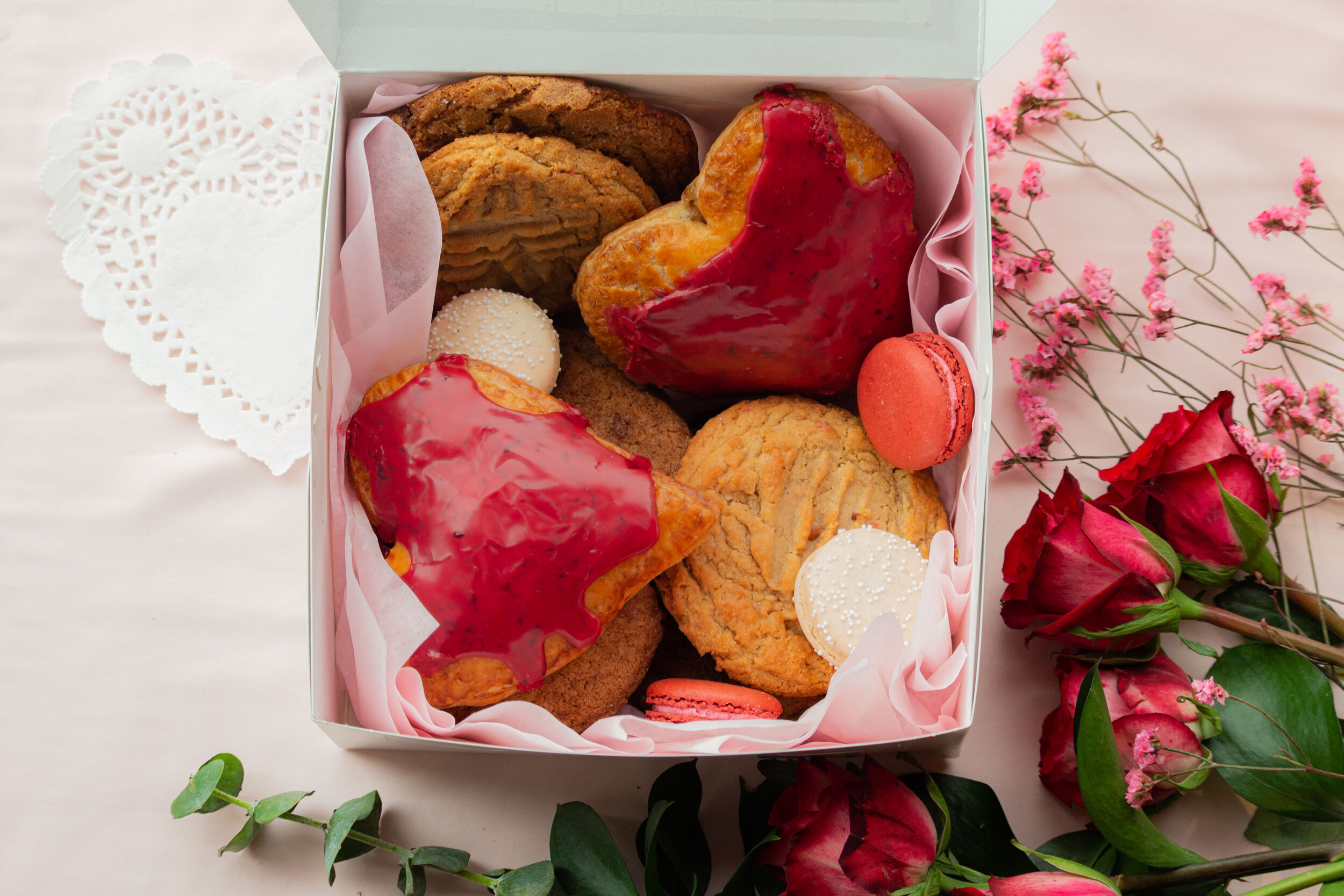 On a pink cloth with roses, a box is filled with heart-shaped and round cookies for Valentine's Day.