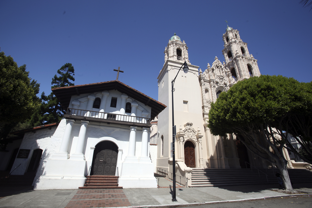 Mission Dolores, a late 18th century Catholic Church in San Francisco, a small white chapel building with a peaked roof with a cross mounted on top next to a much taller temple building with twin spires.