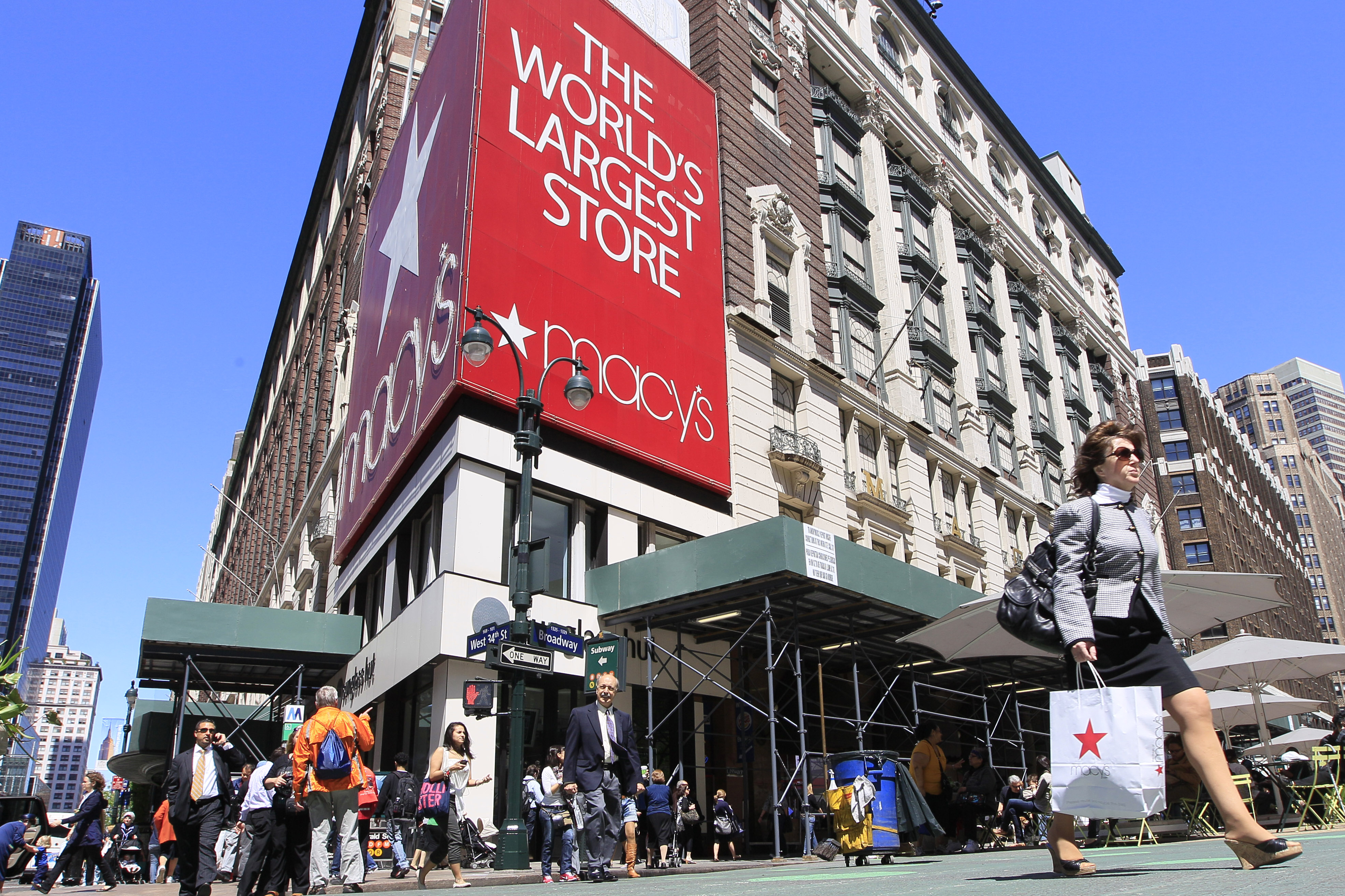 People carrying Macy's shopping bags walk past the Macy's flagship store, Tuesday, May 10, 2011 in New York. Macy's, Inc. reported Wednesday, May 11, strong sales, earnings and cash flow for the first quarter of 2011. (AP Photo/Mary Altaffer)