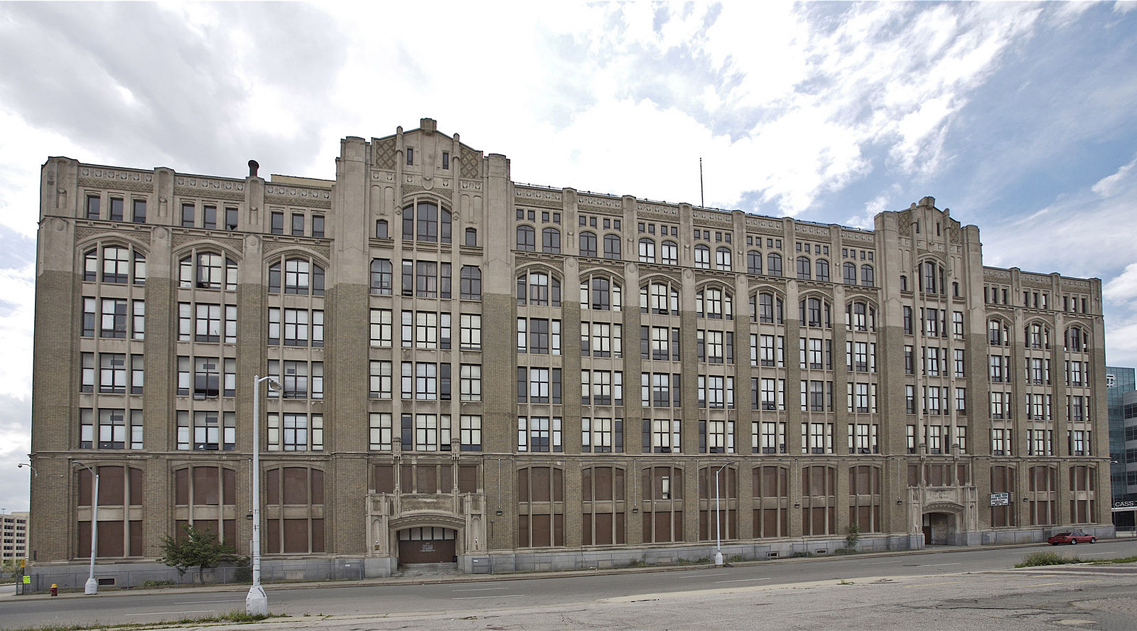 A long brick and limestone building with multiple windows and floors. The first two stories are boarded up.
