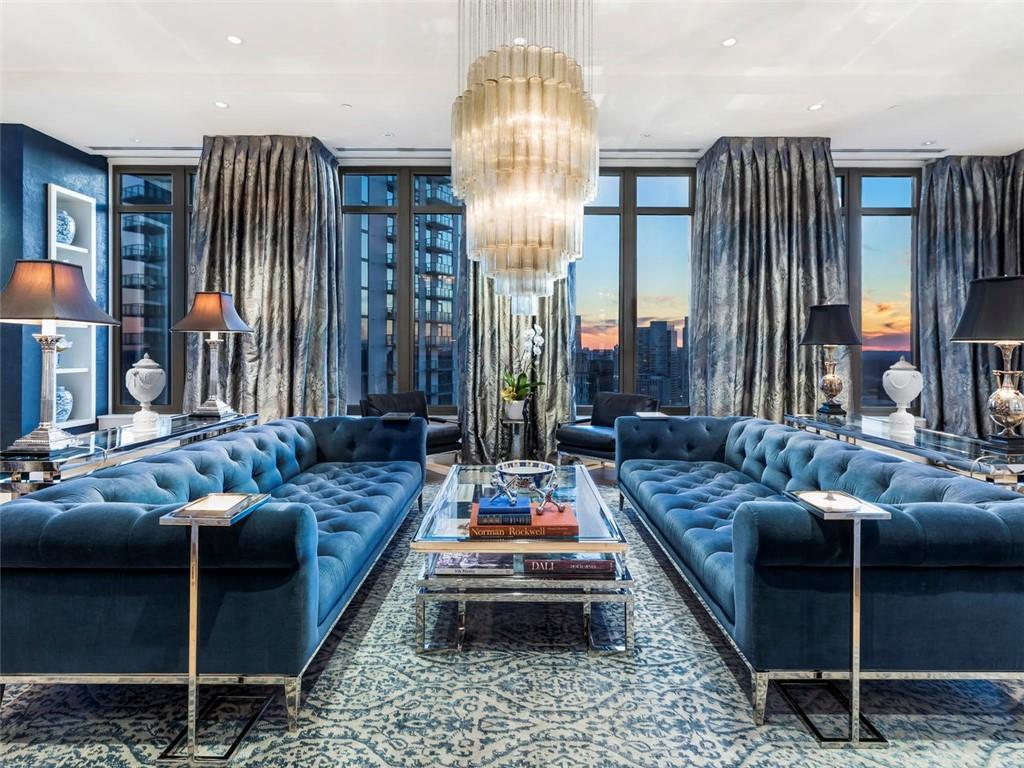 A lavish condo high in the sky with two large blue couches.